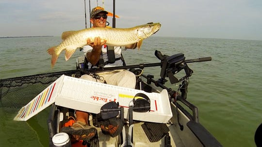 Richard Ofner shows off a muskie he caught while fishing in a kayak.
