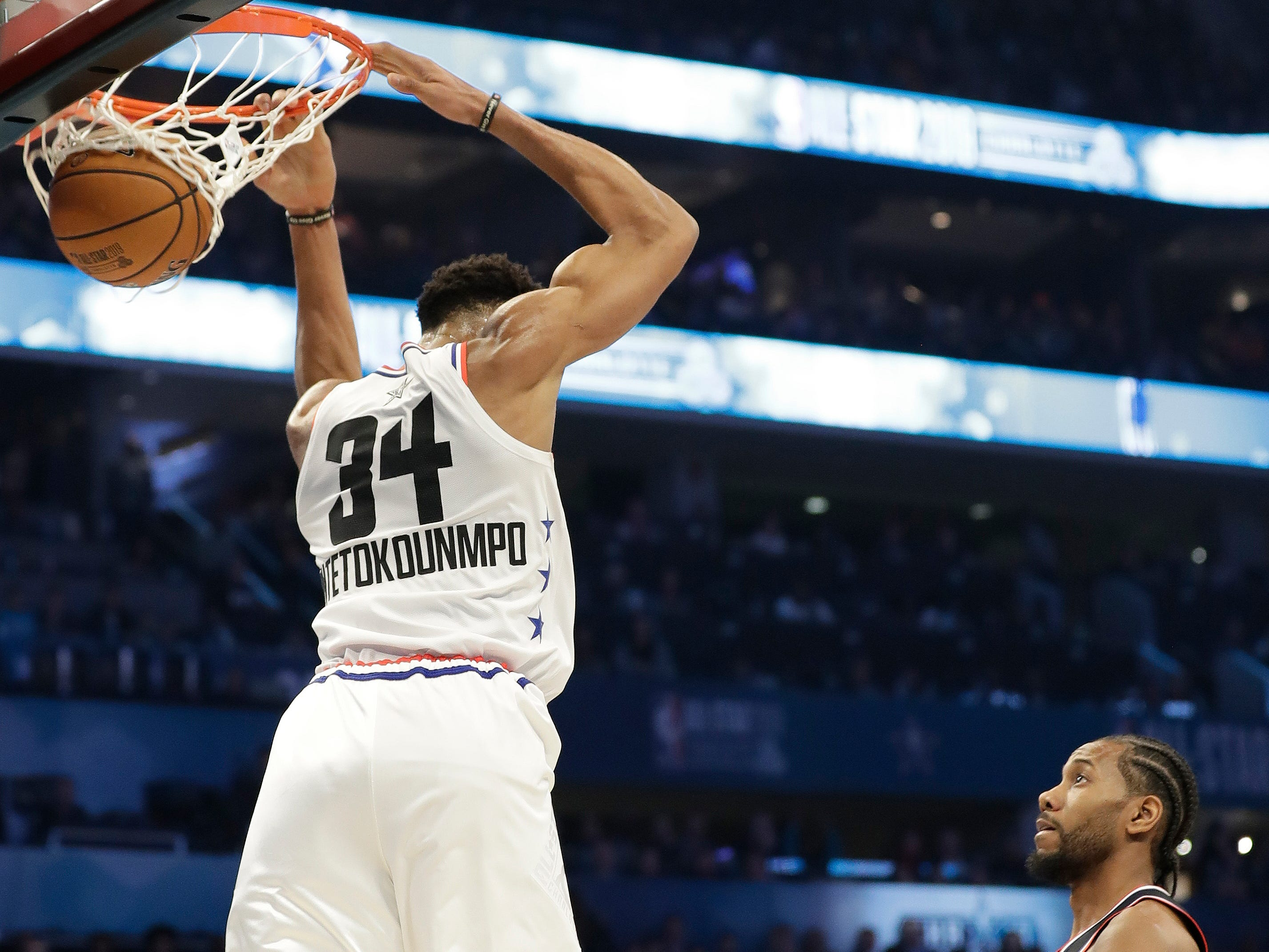 Giannis Antetokounmpo dunks over his head in the first half on Sunday night.