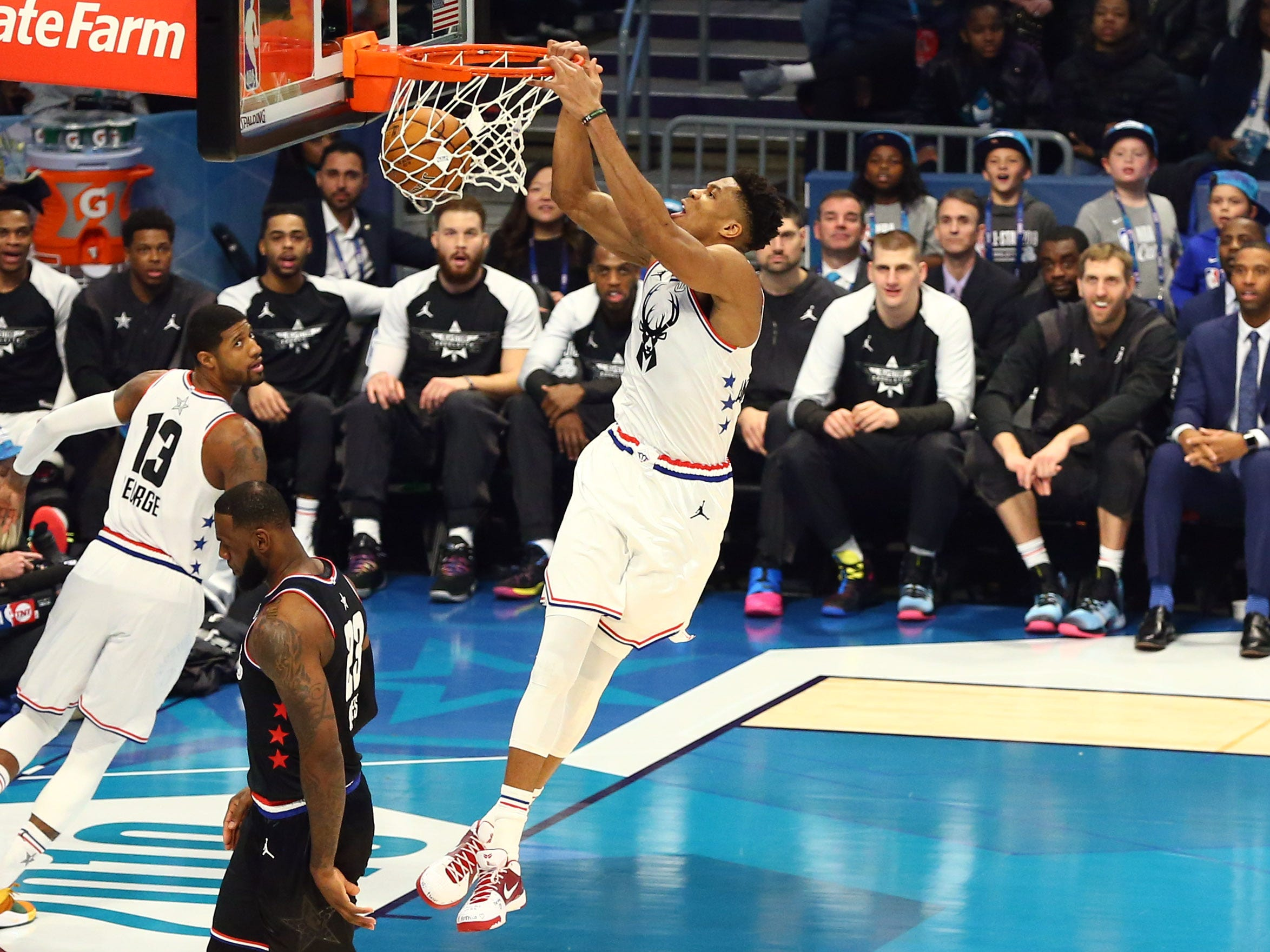 Giannis Antetokounmpo of the Milwaukee Bucks hangs on the rim after one of his 11 dunks on Sunday night in the NBA All-Star Game.