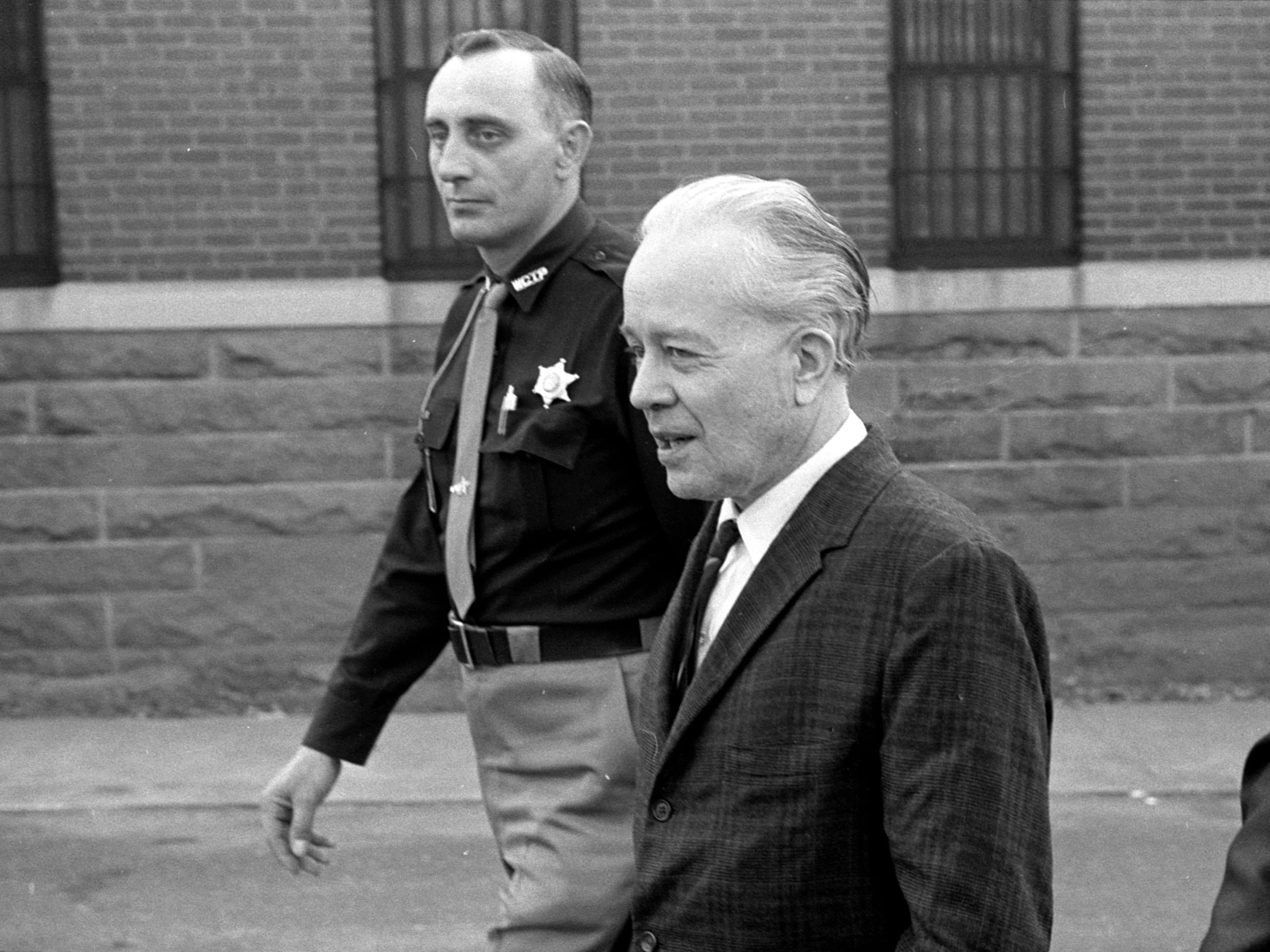 A Waushara county sheriff's deputy led Ed Gein from the courthouse in Wautoma after he was found not guilty by reason of insanity in the 1957 slaying of a Plainfield widow and recommitted to the central state hospital.