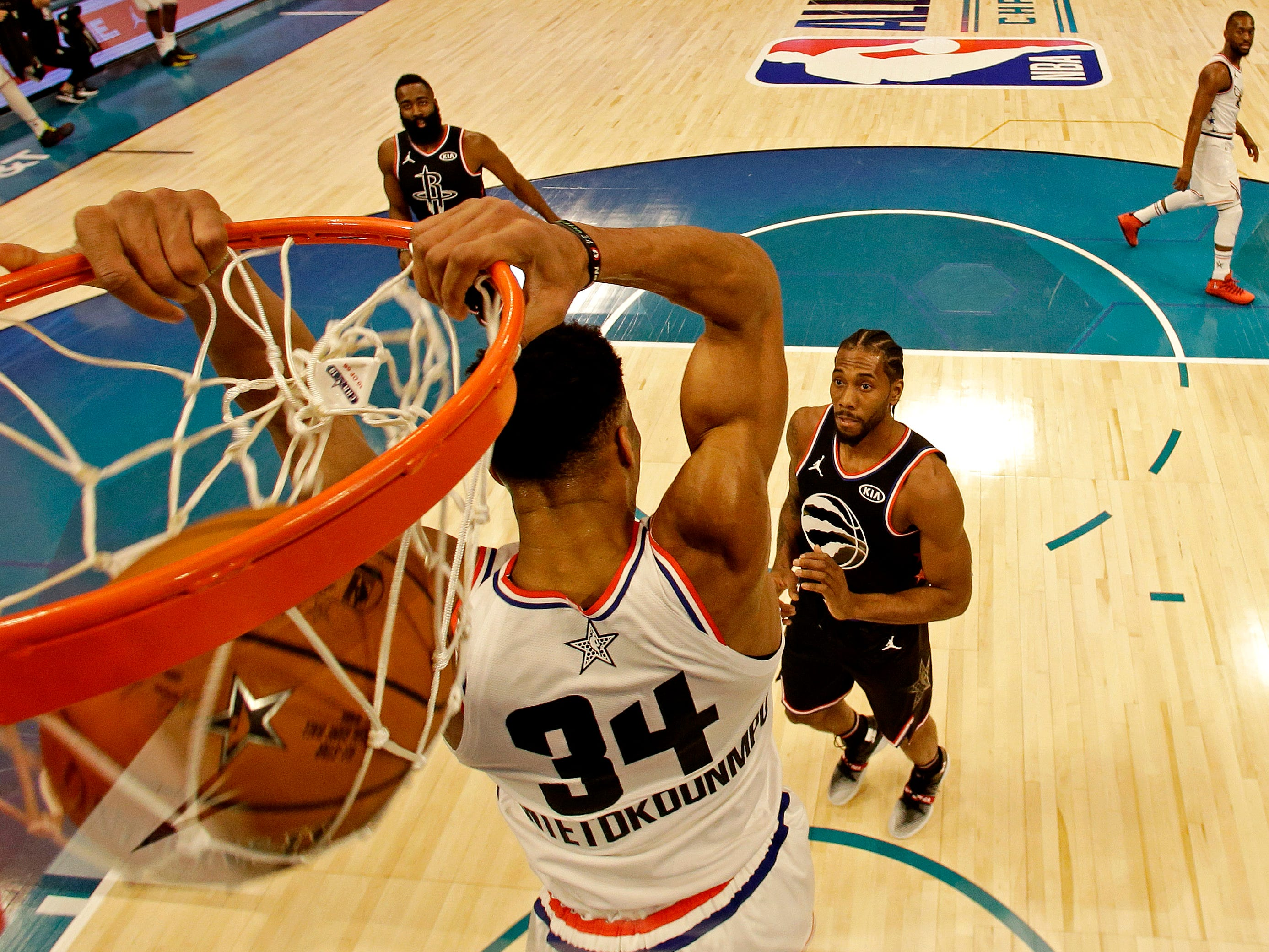 Giannis Antetokounmpo hangs on the rim after dunking the ball behind his head on Sunday night.