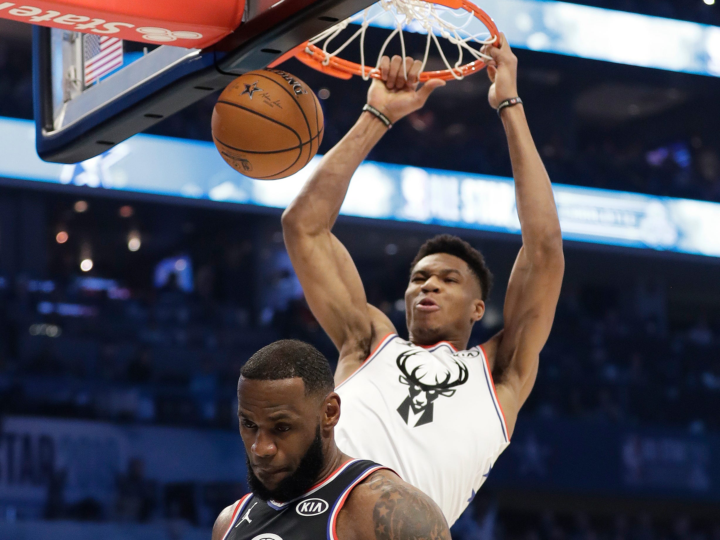 Giannis Antetokounmpo, of the Milwaukee Bucks, dunks the ball as LeBron James moves out of the way.