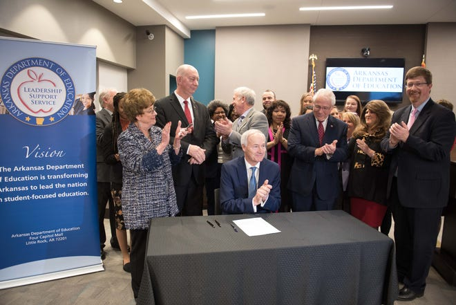 Gov. Asa Hutchinson (seated) gets a round of applause after he signed House Bill 1145 into law Monday afternoon at the state Department of Education. The bill will raise the base teacher's salary statewide to $32,800 next year and up to $36,000 by 2023.