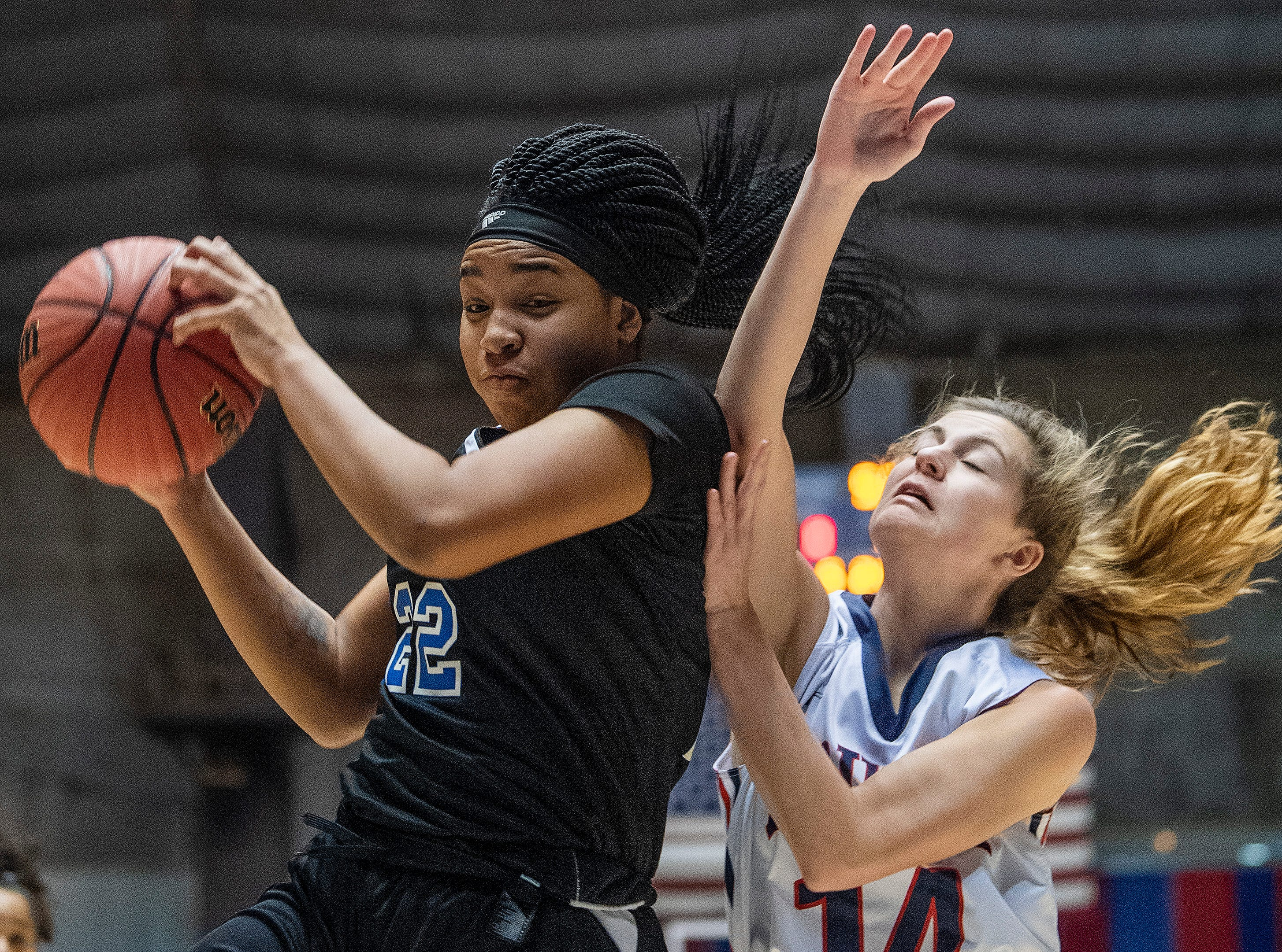 Childersburg's Keasia McKinney grabs a rebound over Trinity's Kenslee Harrison in AHSAA Regional action at Garrett Coliseum in Montgomery, Ala., on Monday February 18, 2019.