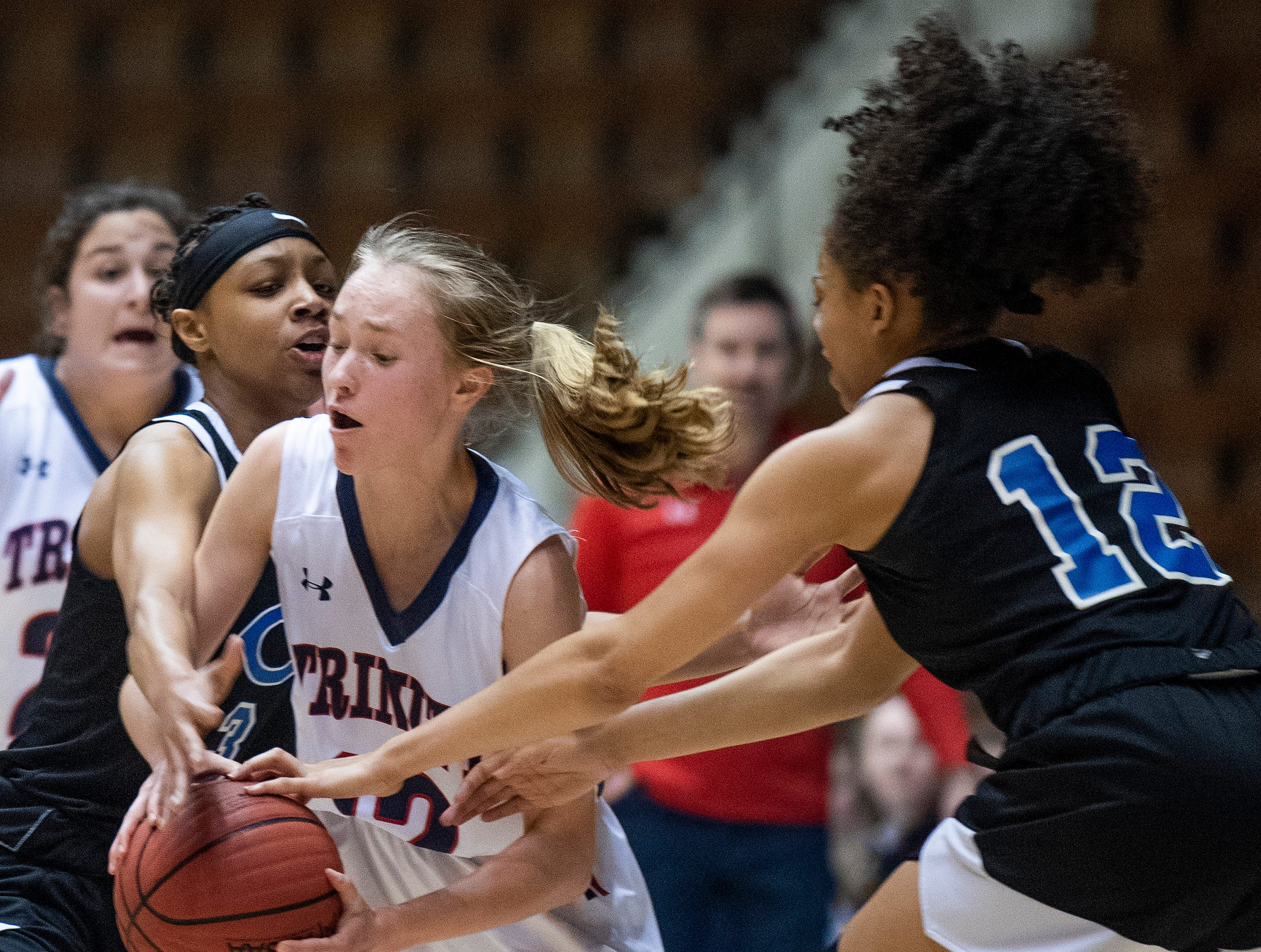 Trinity's Emma Kate Smith is double teamed by Childersburg's Eunique McKinney and Jailah Swain in AHSAA Regional action at Garrett Coliseum in Montgomery, Ala., on Monday February 18, 2019.