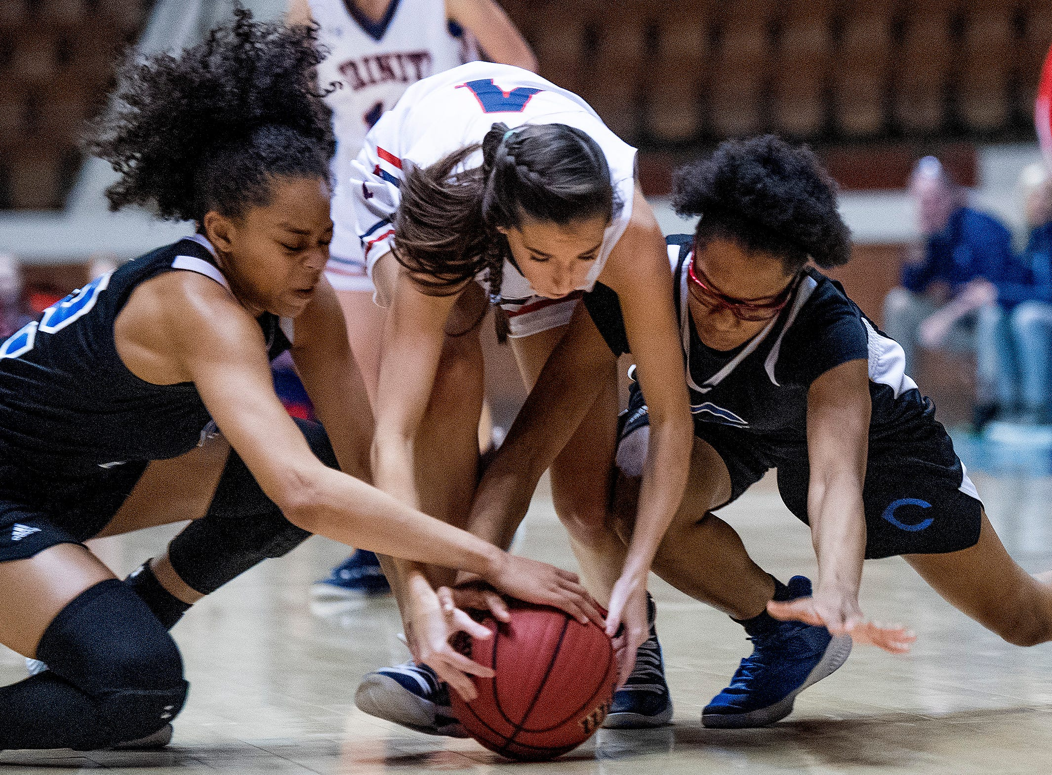 Childersburg's Keasia McKinney and Aubrey Foy fight for the ball with Trinity's Brooke Avant in AHSAA Regional action at Garrett Coliseum in Montgomery, Ala., on Monday February 18, 2019.