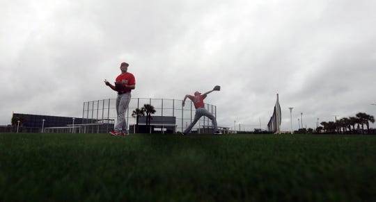 Boston Red Sox starting pitchers Nathan Eovaldi, left, and Chris Sale, warm up in the rain as pitchers and catchers report for their first workout at their spring training baseball facility in Fort Myers on Wednesday, Feb. 13.