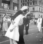 In this Aug. 14, 1945 file photo provided by the U.S. Navy, a sailor and a woman kiss in New York's Times Square, as people celebrate the end of World War II. The ecstatic sailor shown kissing a woman in Times Square celebrating the end of World War II has died. George Mendonsa was 95. It was years after the photo was taken that Mendonsa and Greta Zimmer Friedman, a dental assistant in a nurse's uniform, were confirmed to be the couple.