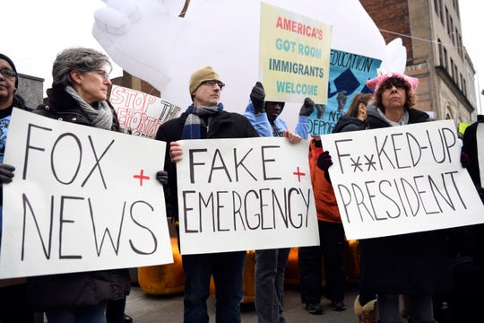 Demonstrators hold up signs during a protest on Monday, Feb. 18, 2019, in Newark. Towns across New Jersey held protests in response to President Donald Trump's national emergency declaration that would allow him to use military funds to build a wall at the southern border.
