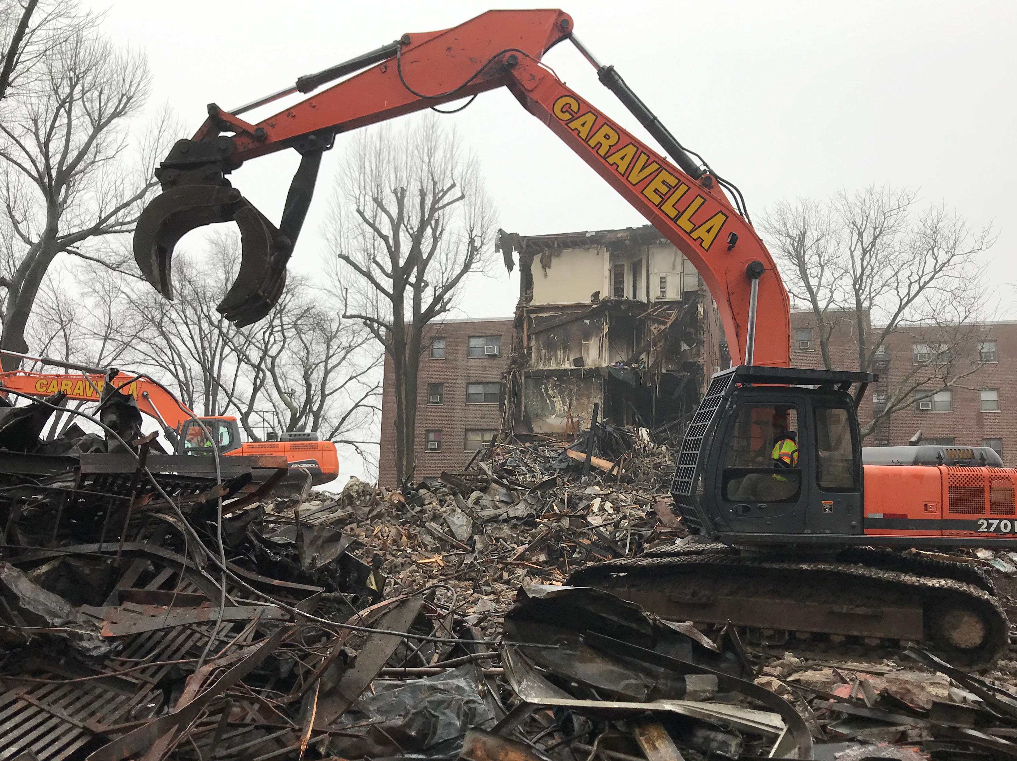 Demolition equipment is tearing down part of the apartment complex that was heavily damaged by the fire that broke out on February 14, 2019. irefighters are hitting hot spots the morning after a fire broke out at an apartment complex on Edwin Ave in Fort Lee on Monday February 18, 2019.