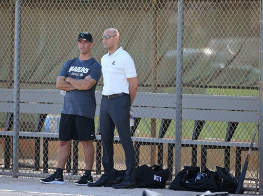 Miami Marlins Special advisor to baseball operations Jorge Posada, left, and Marlins Chief Executive Officer Derek Jeter talk during a workout at the team's spring training baseball facility in Jupiter, Fla., Monday, Feb. 18, 2019, (David Santiago/Miami Herald via AP)