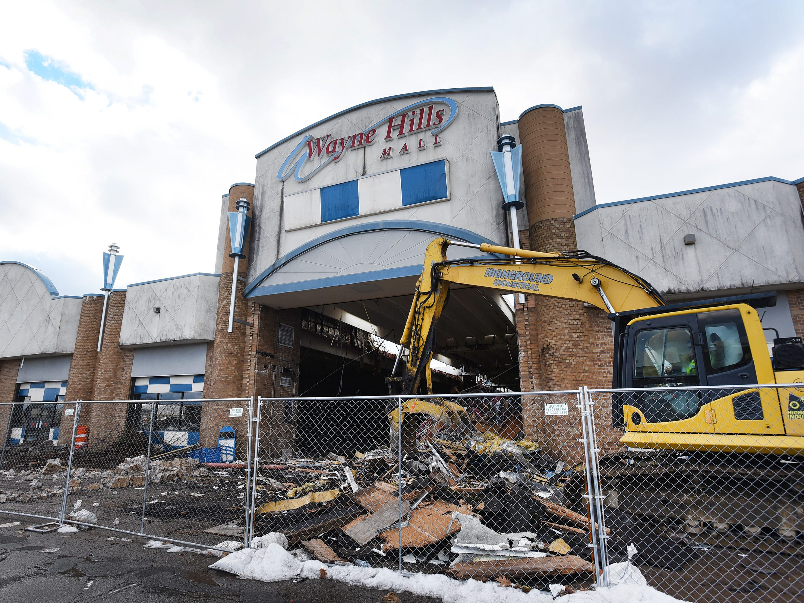 A worker operates an excavator to demolish Wayne Hills Mall on Monday.