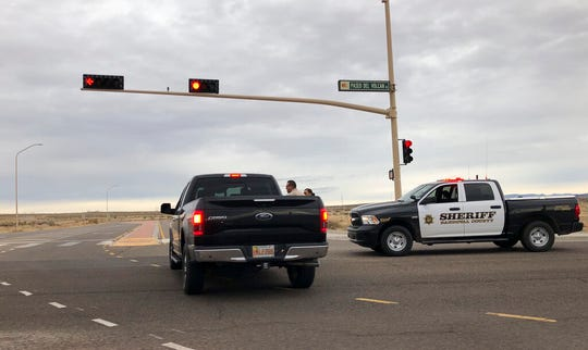 A Sandoval County sheriff's deputy stops a motorist near Sue Cleveland High School in Rio Rancho, N.M. on Thursday, Feb. 14, 2019. Rio Rancho police say a gunshot was fired at the high school in that Albuquerque suburb but that nobody was injured and that one person is in custody.