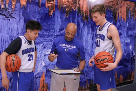 Carlsbad head coach Jamaal Brown goes over a play diagram with seniors Pat Espinoza (21) and Stevie Bartlett (13) . The duo of Espinoza and Bartlett will play their final home game this Friday against Hobbs.