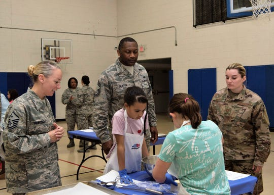 Airmen from the 49th Mission Support Group watch team Chipies mix cookie dough, Jan. 30, 2019, on Holloman Air Force Base, N.M. Five teams from the Youth and Teen Center participated in a cookie baking challenge to win golden spatulas.