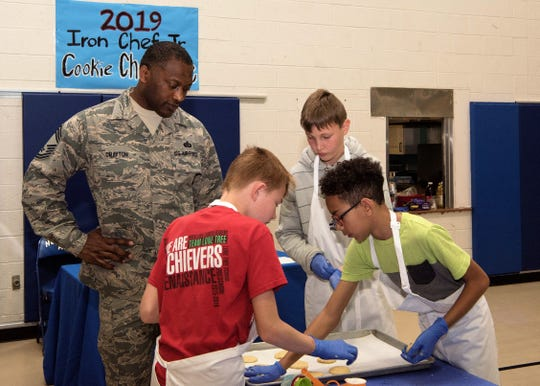 Chief Master Sgt. Bobby Drayton, 49th Force Support Squadron superintendent, watches team Papyrus' Cookie Corner place sugar cookies on a baking sheet, Jan. 30, 2019, on Holloman Air Force Base, N.M. Seventeen members of the Youth and Teen Center signed up for a cookie baking competition and the competition lasted two and a half hours.