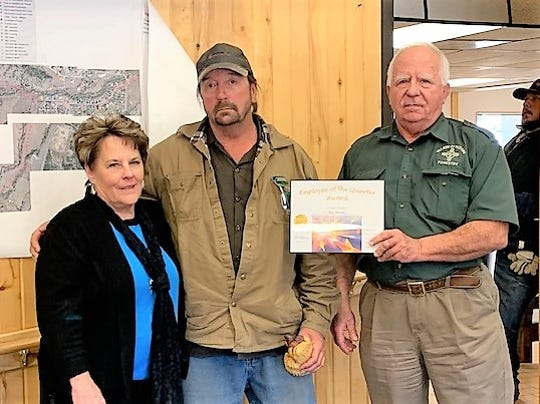 Eric Annala, center, received his award from forestry director Dick Cooke and Village Manager Debi Lee.
