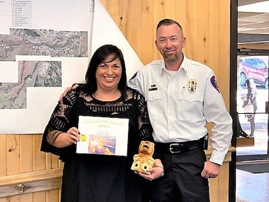 Ruidoso Fire Chief Cody Thetford gave Elaine Reynolds her award as administrative employee of the quarter.