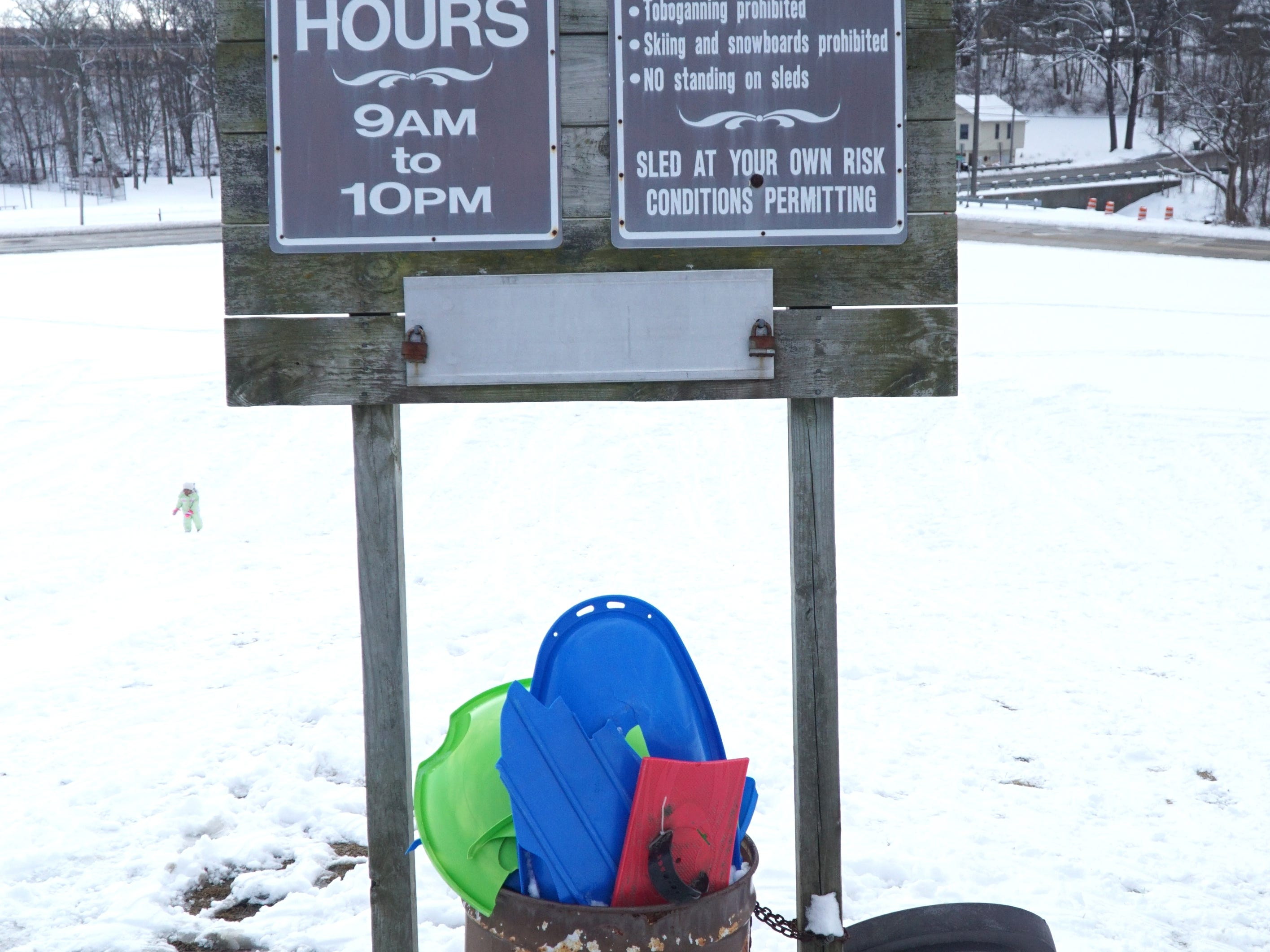 A sign of rules and a trash can filled with broken plastic sled greets visitors to Farmington's Sled Hill off Shiawasee on Feb. 18. There were dozens of sledders taking advantage of the snow fall from the previous day - plus Farmington schools were out for their mid-winter break.