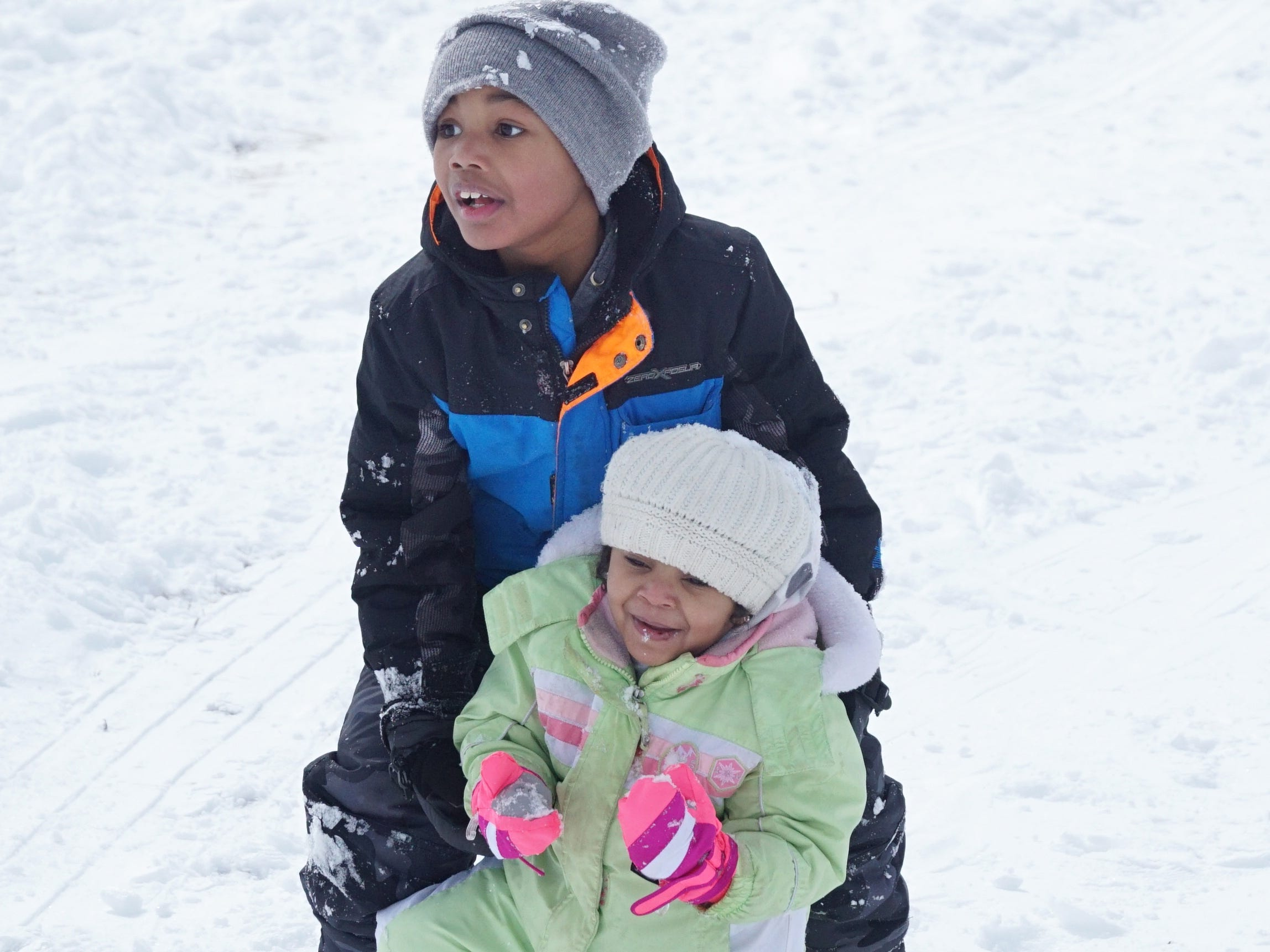 Eiljah Marbry, 6, helps his baby sister Elise, 3, up the hill as the two were sledding in Farmington on Feb. 18.