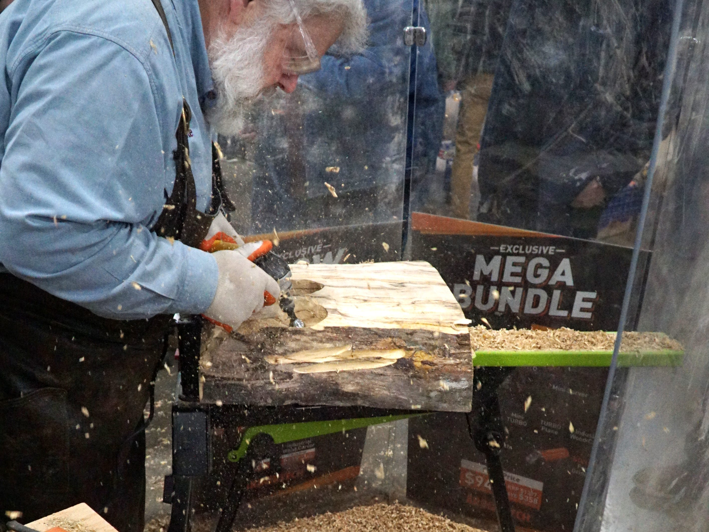 A big pile of woodchips gathers at the feet of Mike VanBelt as he uses a disc cutting tool to work on a slab of wood.