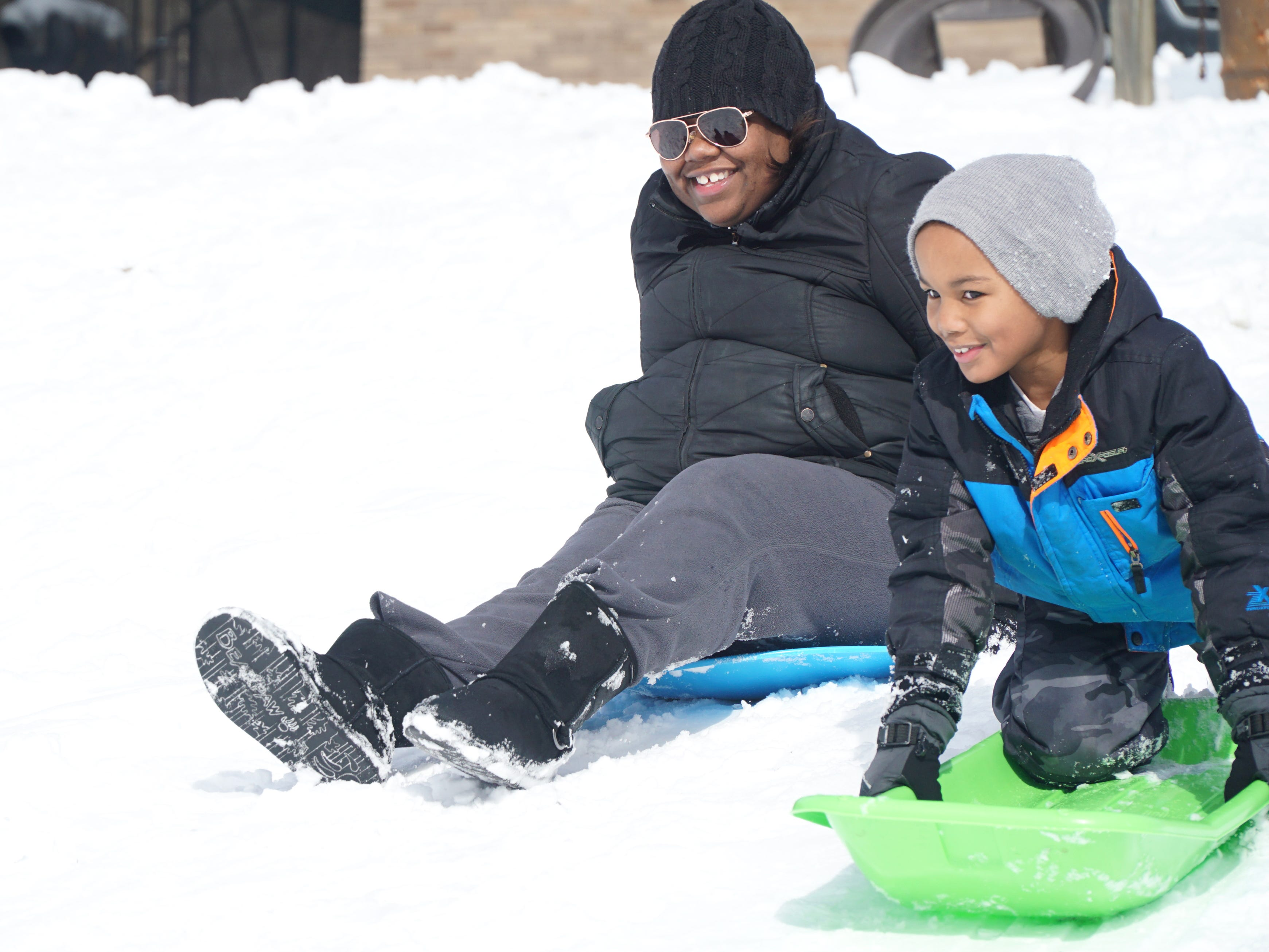 Shara Marbry races her son Elijah, 6, to the bottom of the Sled Hill on Shiawasee in Farmington.