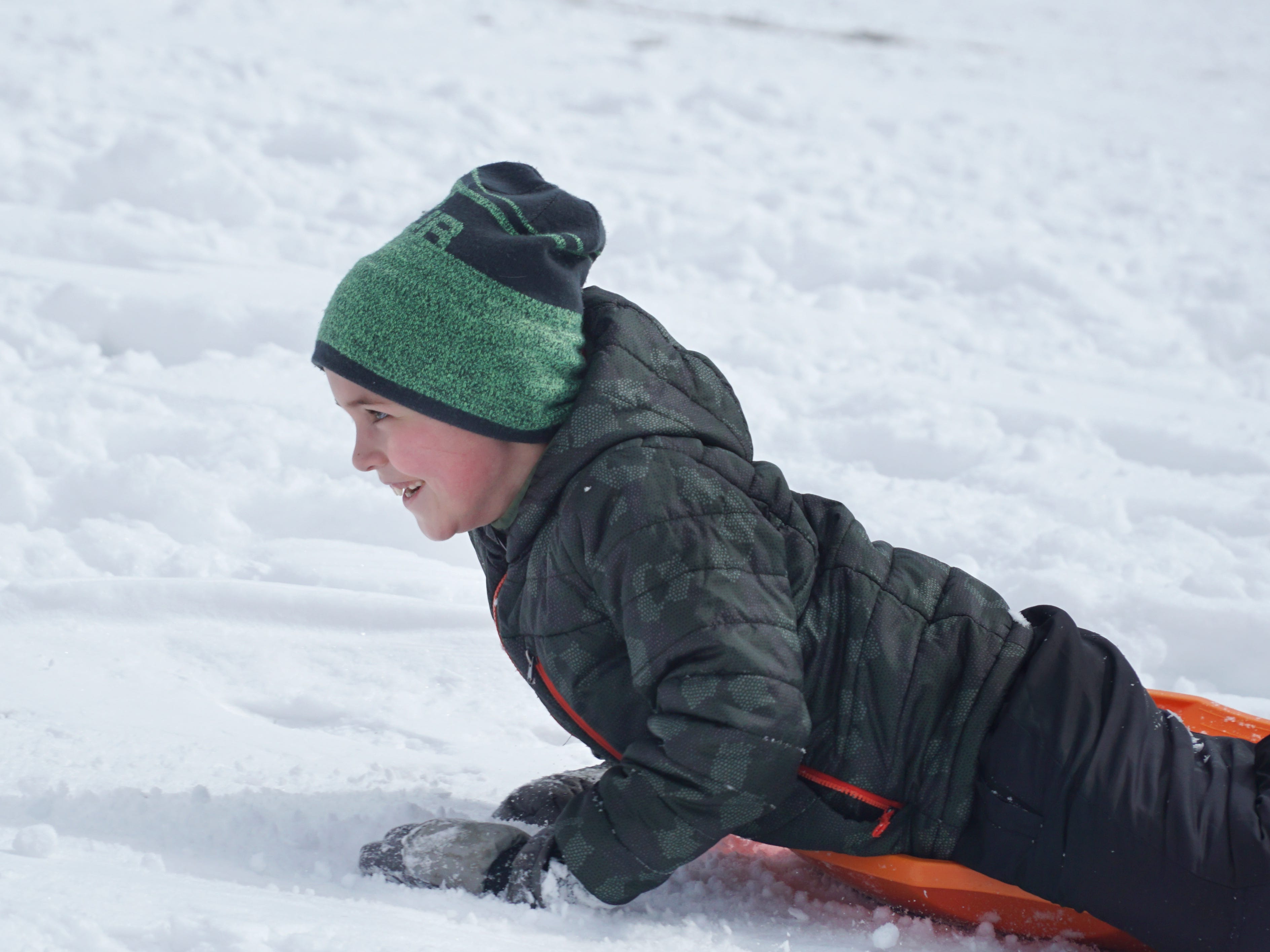 Mason Latimer, 7, smiles as he begins to head downhill backwards while sledding in Farmington on Feb. 18.