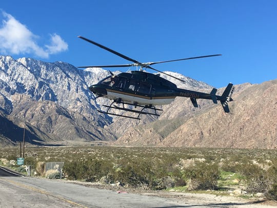 A helicopter airlifts staff to the Palm Springs Aerial Tramway station. A storm damaged the road to the tram and the tourist attraction is closed indefinitely.