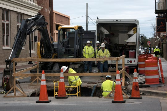 Electrical contractors work on upgrading the underground utilities on Romana Street in downtown Pensacola on Monday.