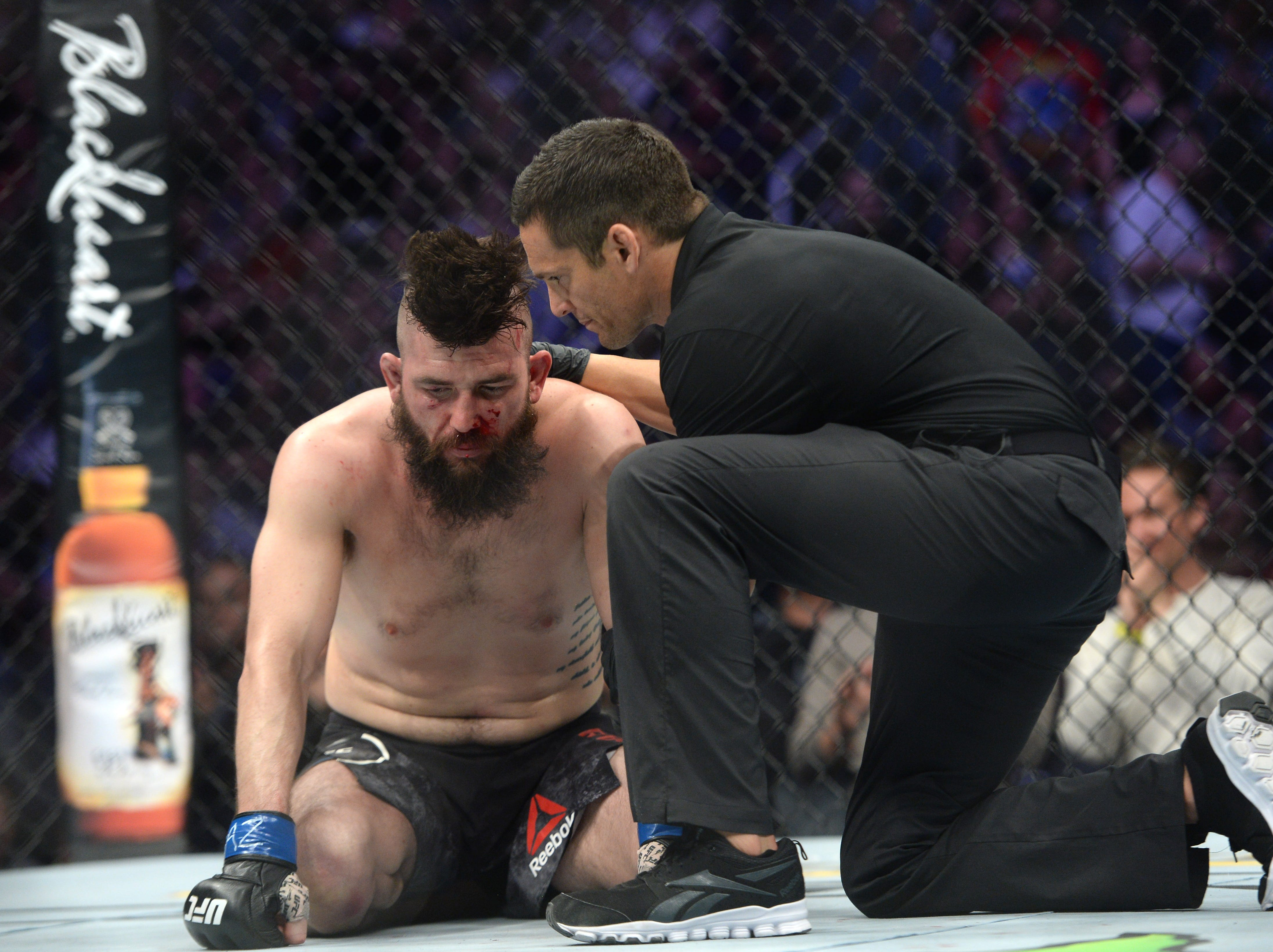 Feb 17, 2019; Phoenix, AZ, USA; Bryan Barberena (blue) is tended to after his welterweight bout against Vicente Luque  (not pictured) during UFC Fight Night at Talking Stick Resort Arena. Luque won via third round TKO. Mandatory Credit: Joe Camporeale-USA TODAY Sports