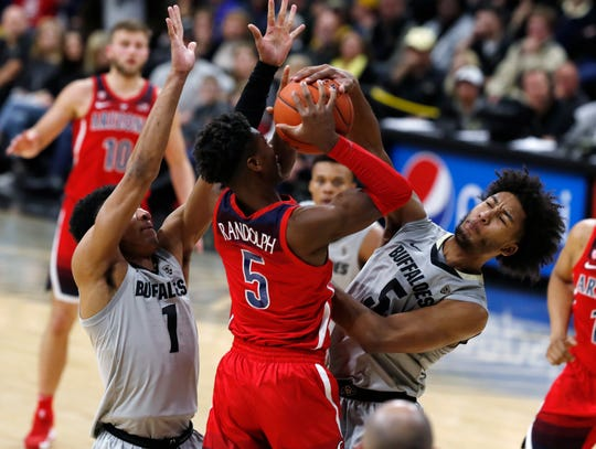 Colorado guard D'Shawn Schwartz, right, riches up to block a shot by Arizona guard Brandon Randolph, center, as Colorado guard Tyler Bey defends in the first half of an NCAA college basketball game Sunday, Feb. 17, 2019, in Boulder, Colo.