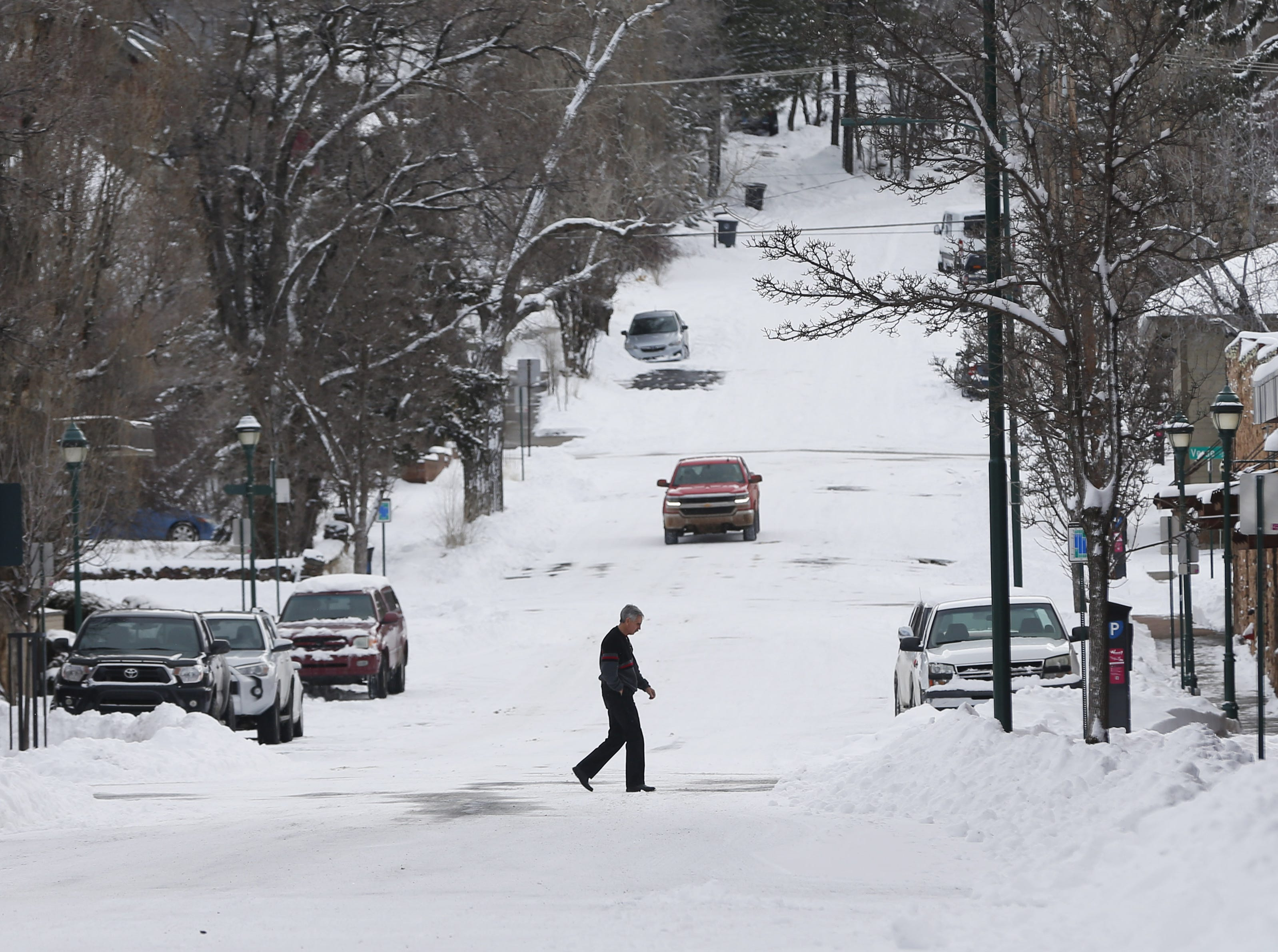 A pedestrian walks in the snow in downtown Flagstaff Feb. 18, 2019.