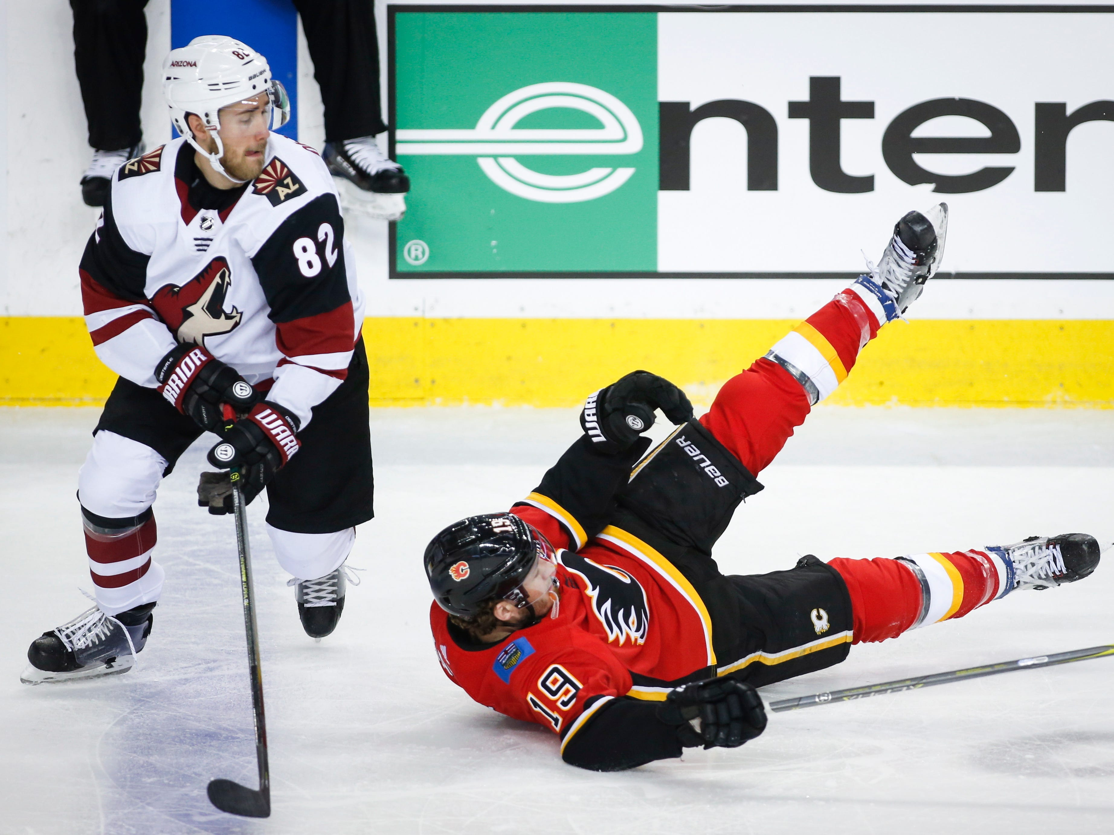 Arizona Coyotes' Jordan Oesterle, left, knocks Calgary Flames' Matthew Tkachuk to the ice during first period NHL hockey action in  Calgary, Alberta, Monday, Feb. 18, 2019.