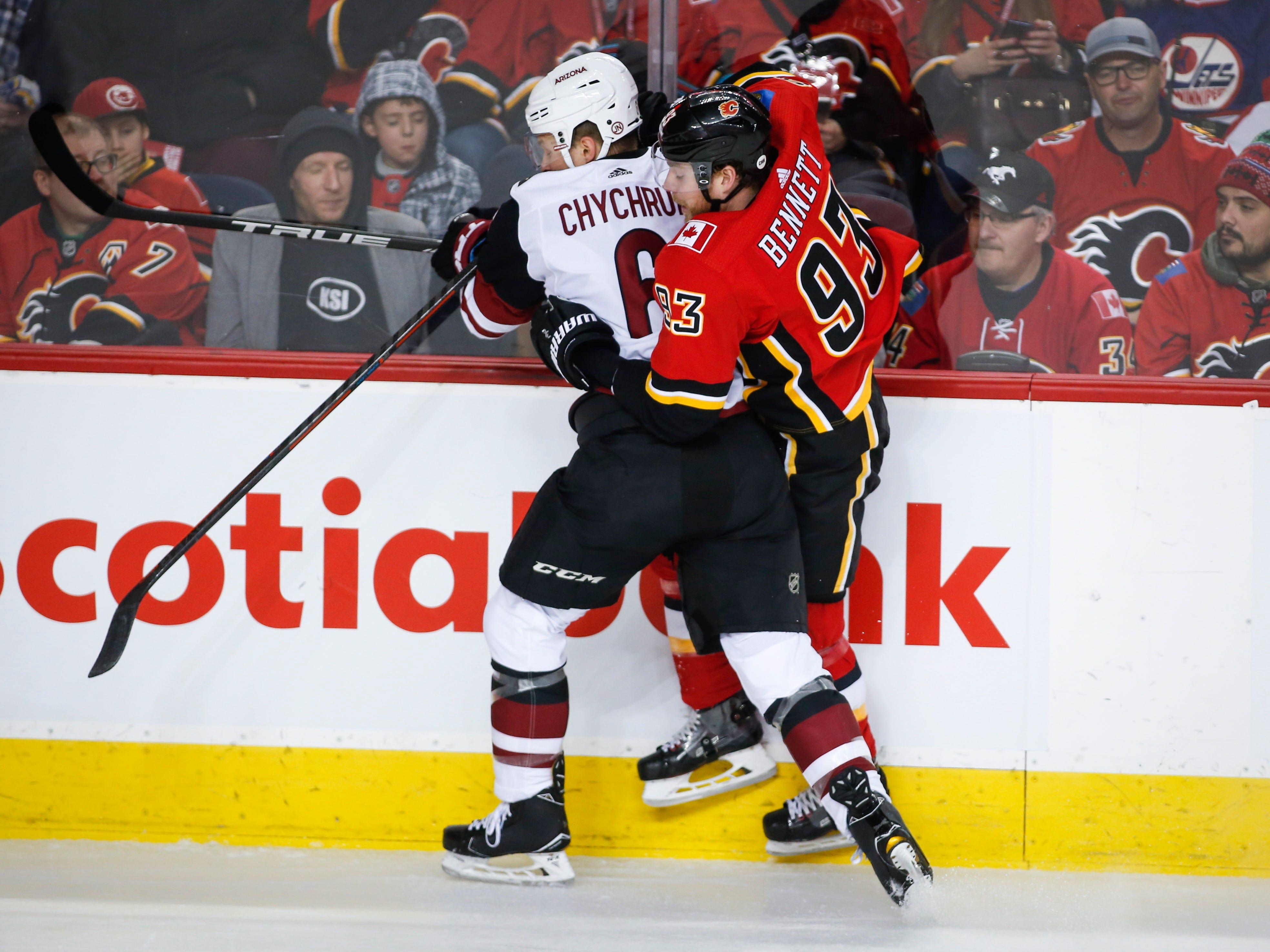 Arizona Coyotes' Jakob Chychrun, left, checks Calgary Flames' Sam Bennett during first period NHL hockey action in Calgary,  Calgary, Alberta, Monday, Feb. 18, 2019.