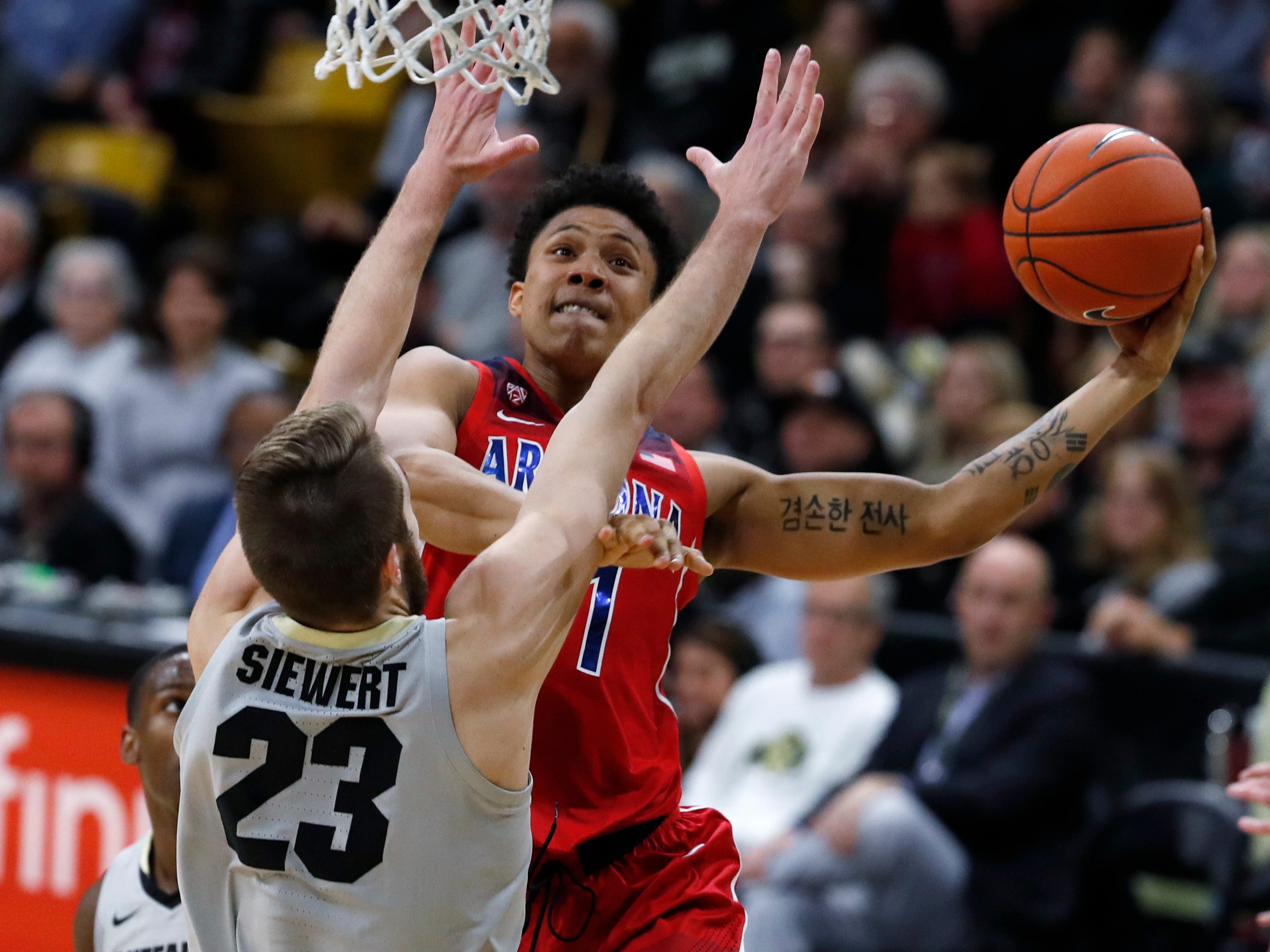 Arizona forward Ira Lee, back drives to the net for a basket as Colorado forward Lucas Siewert defends in the first half of an NCAA college basketball game Sunday, Feb. 17, 2019, in Boulder, Colo.