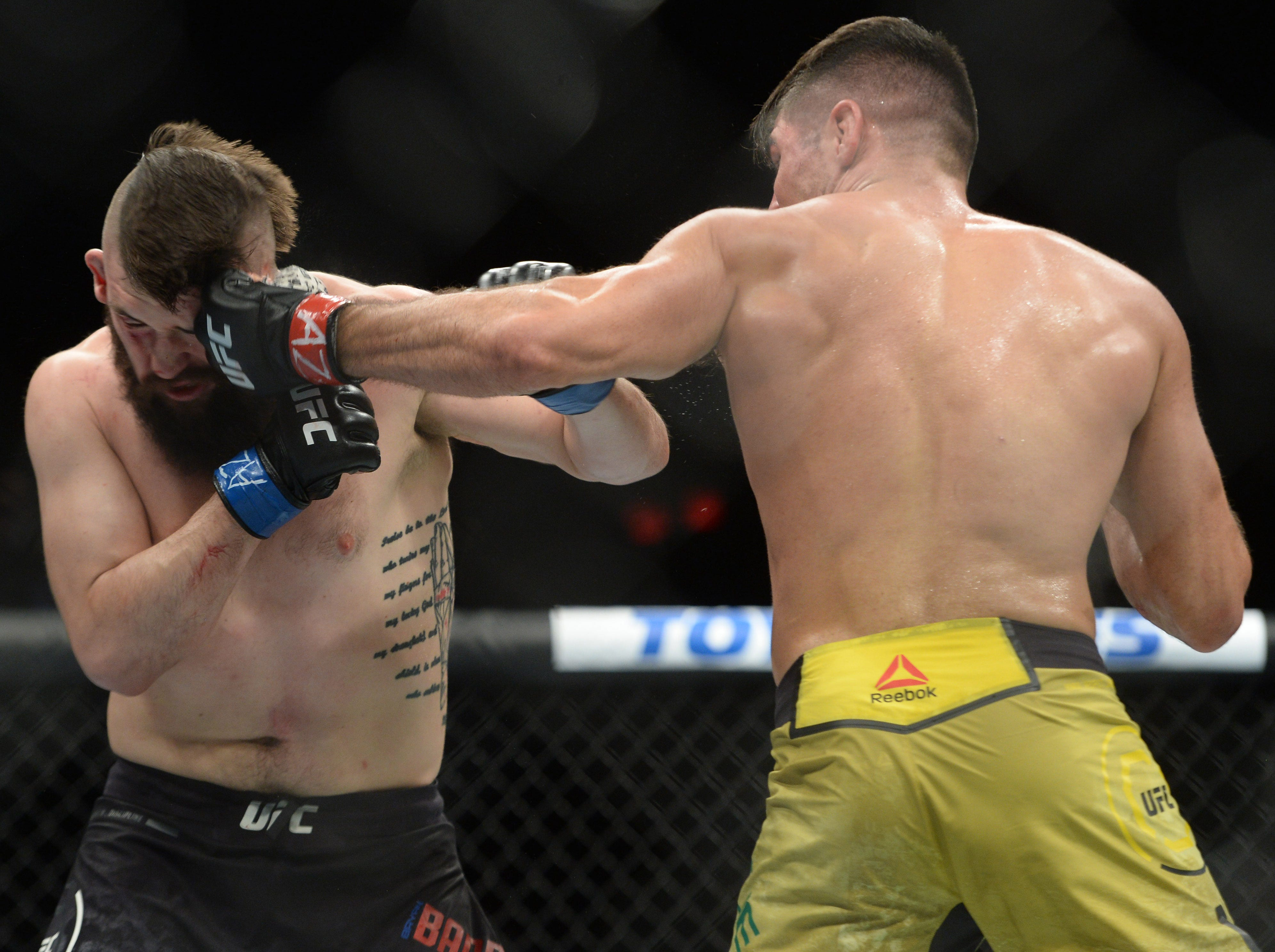 Vicente Luque hits Bryan Barberena with a left hand during their welterweight fight at Talking Stick Resort Arena. Luque won third round with knockout.