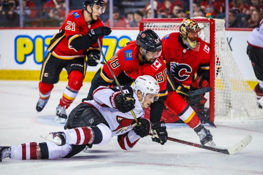Feb 18, 2019: Arizona Coyotes right wing Josh Archibald (45) and Calgary Flames defenseman Oliver Kylington (58) battle for the puck during the second period at Scotiabank Saddledome.