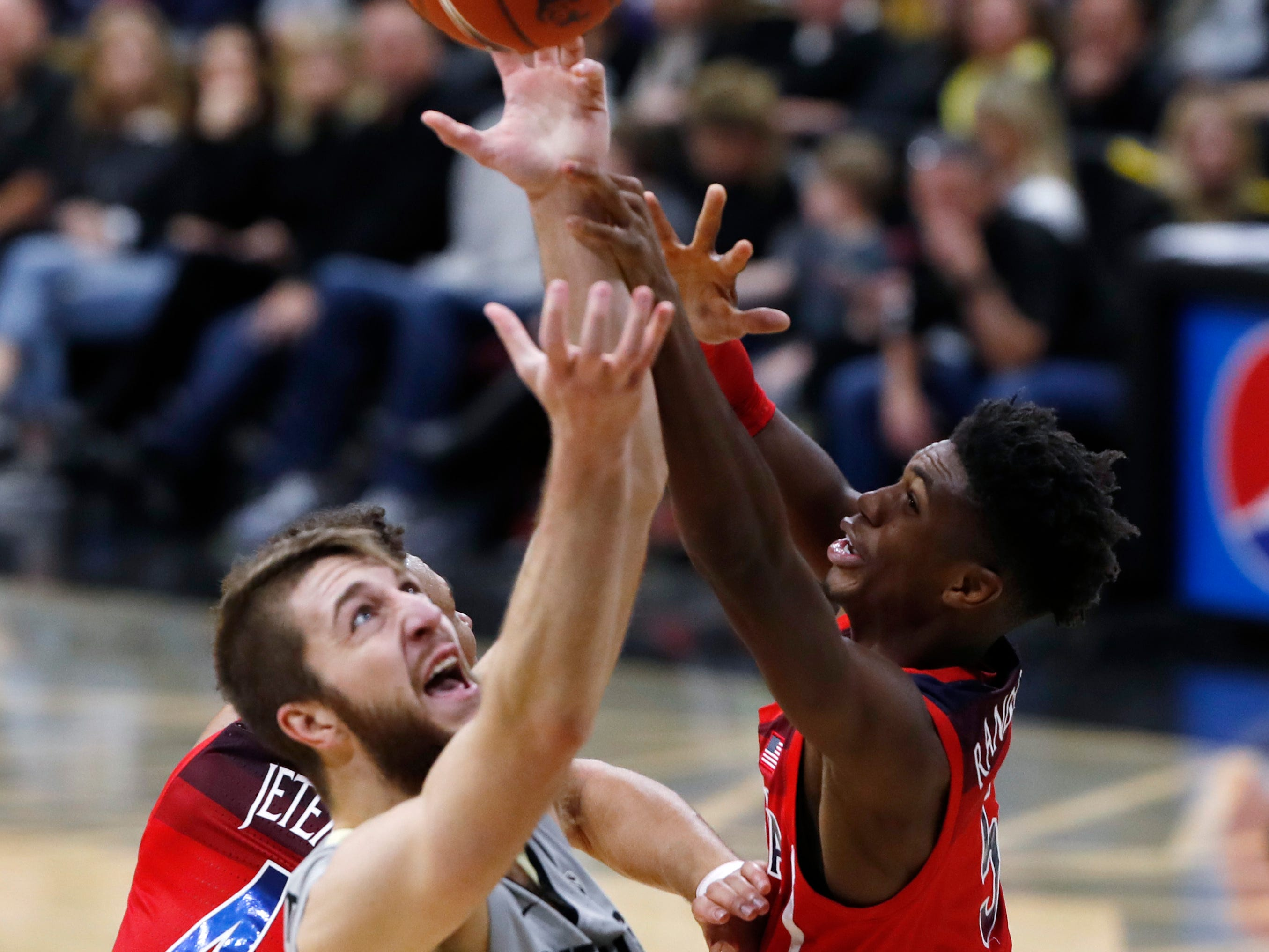 Colorado forward Lucas Siewert, front, pulls in a rebound as Arizona Wildcats center Chase Jeter, back left, and guard Brandon Randolph defend in the second half of an NCAA college basketball game Sunday, Feb. 17, 2019, in Boulder, Colo. Colorado won 67-60.