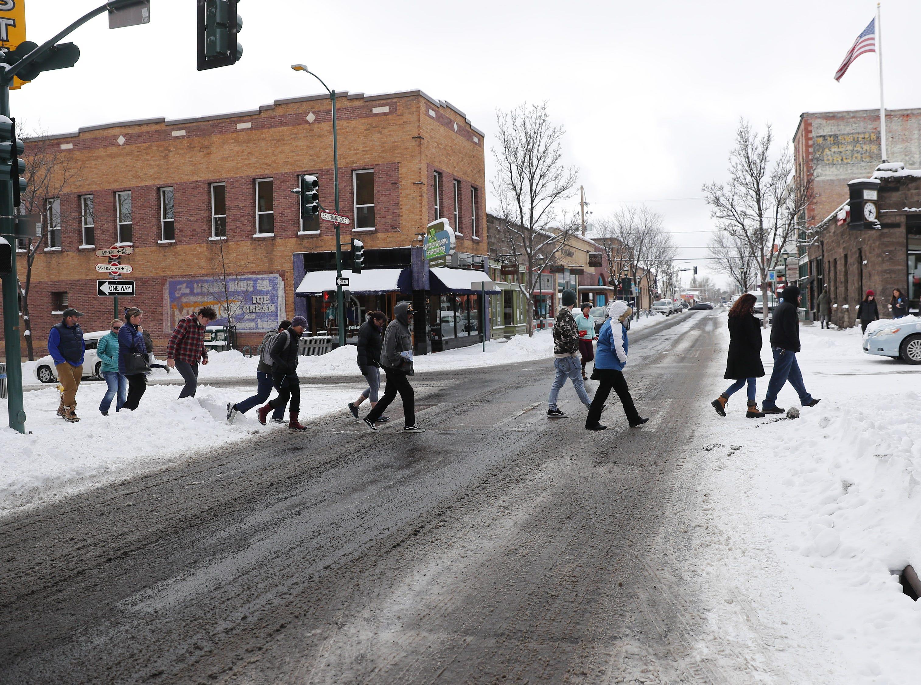 Pedestrians cross San Francisco Street in Flagstaff Feb. 18, 2019.
