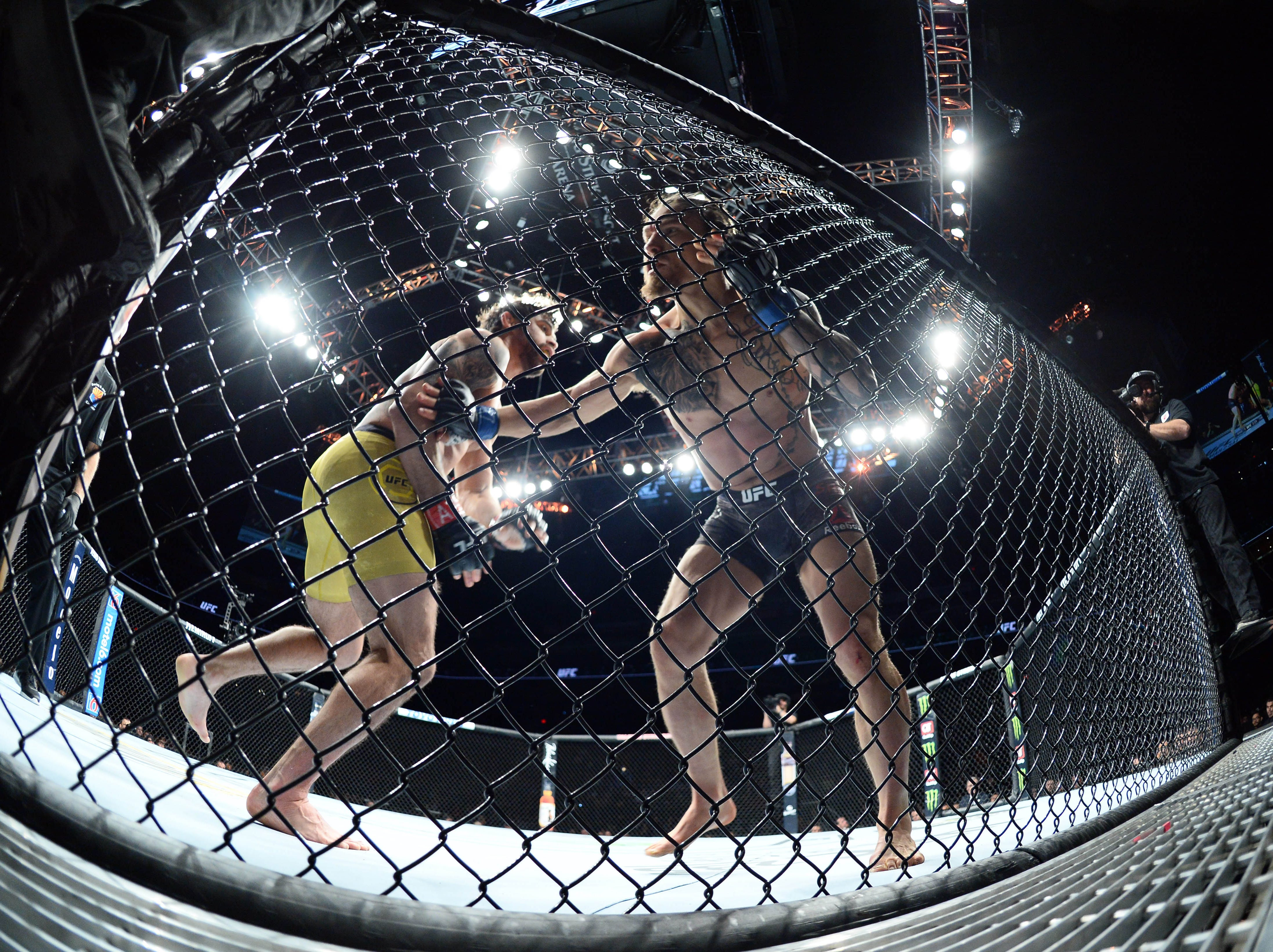Renan Barao (red gloves) and Luke Sanders (blue gloves) spar into the cage during their bantamweight bout at UFC Fight Night at Talking Stick Resort Arena. Sanders won second round finish.