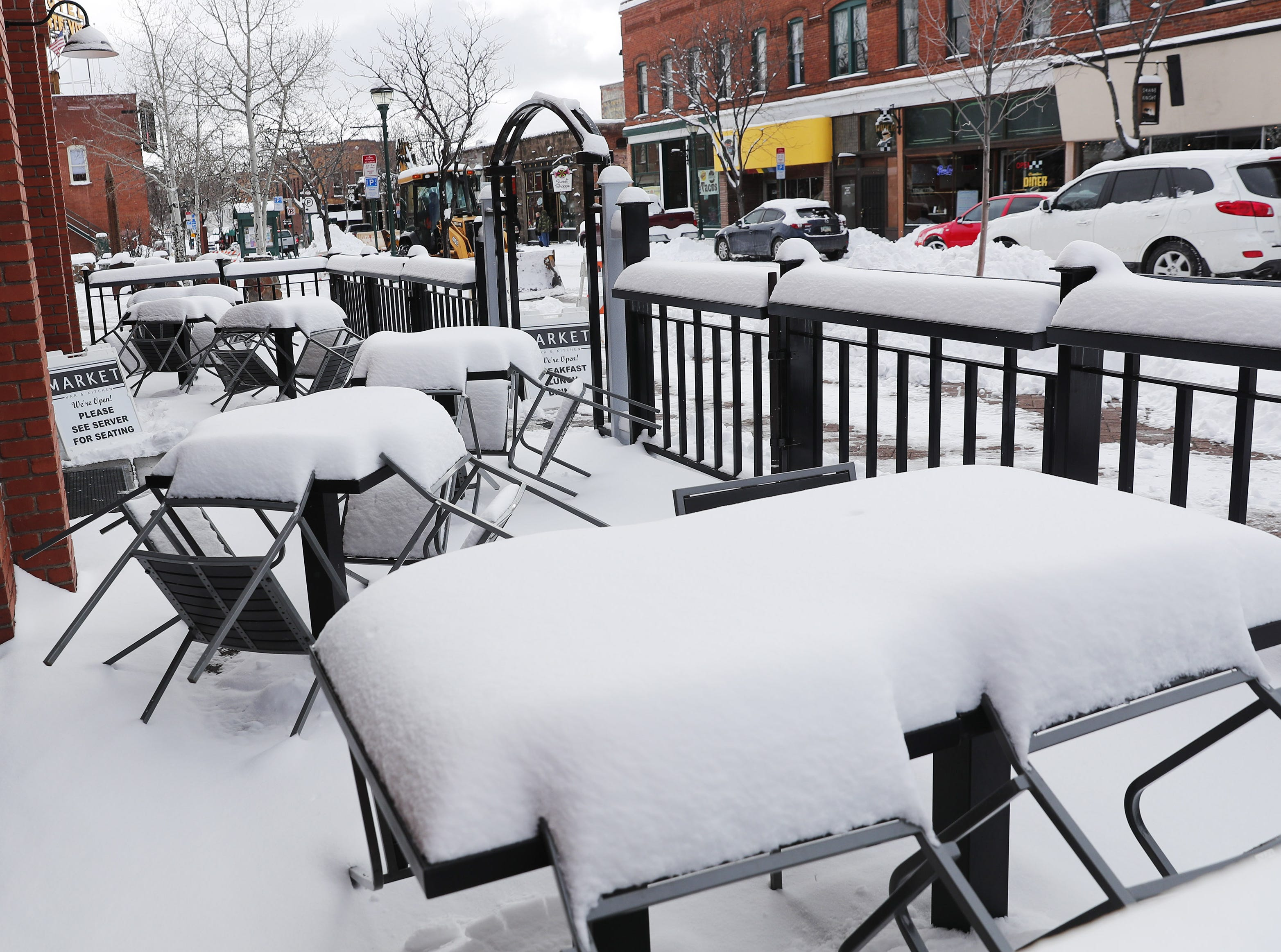 Snow covers tables and chairs on a patio in Flagstaff Feb. 18, 2019.