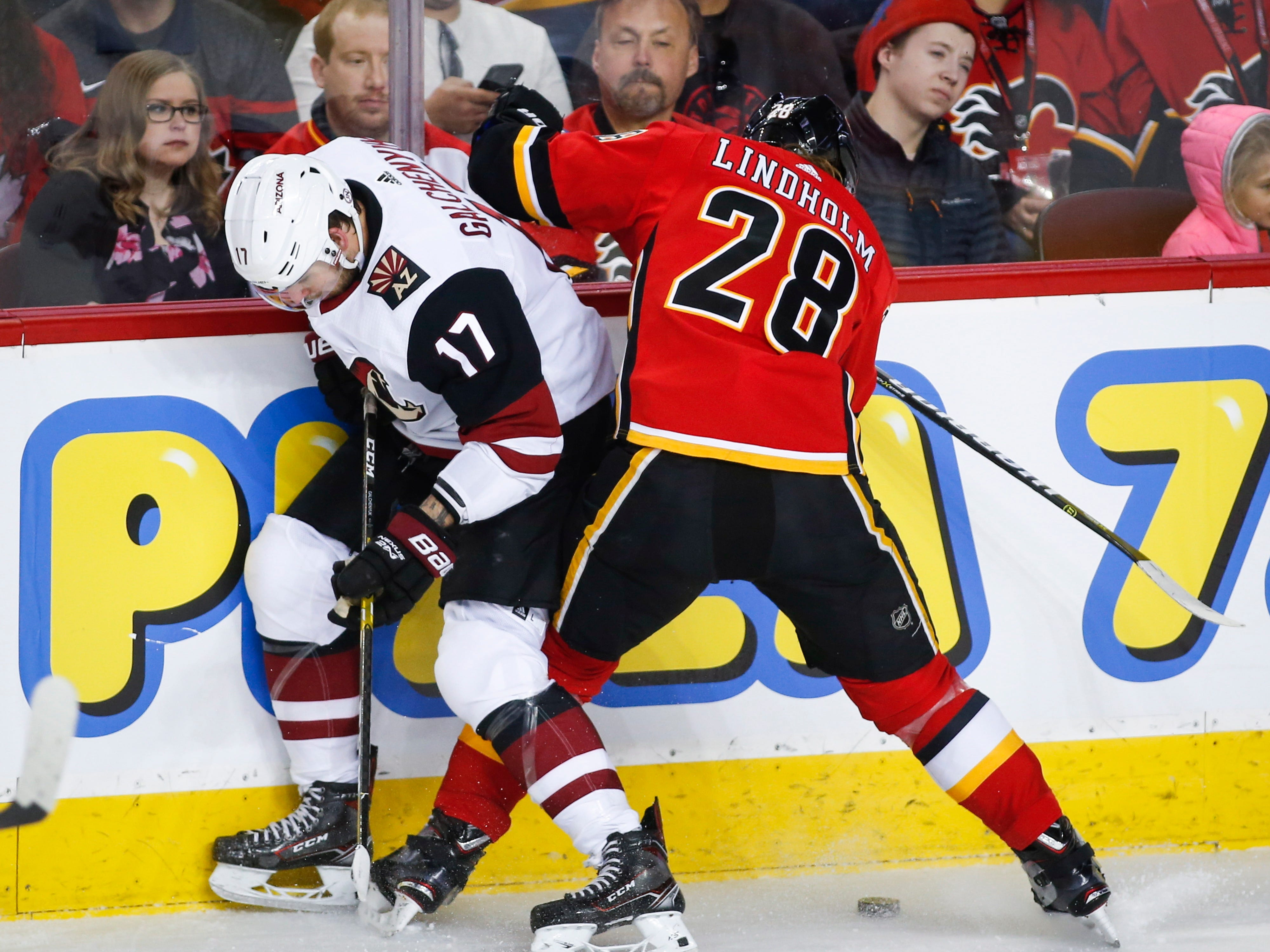 Arizona Coyotes' Alex Galchenyuk, left, battles for the puck with Calgary Flames' Elias Lindholm, of Sweden, during first period NHL hockey action in Calgary,  Calgary, Alberta, Monday, Feb. 18, 2019.