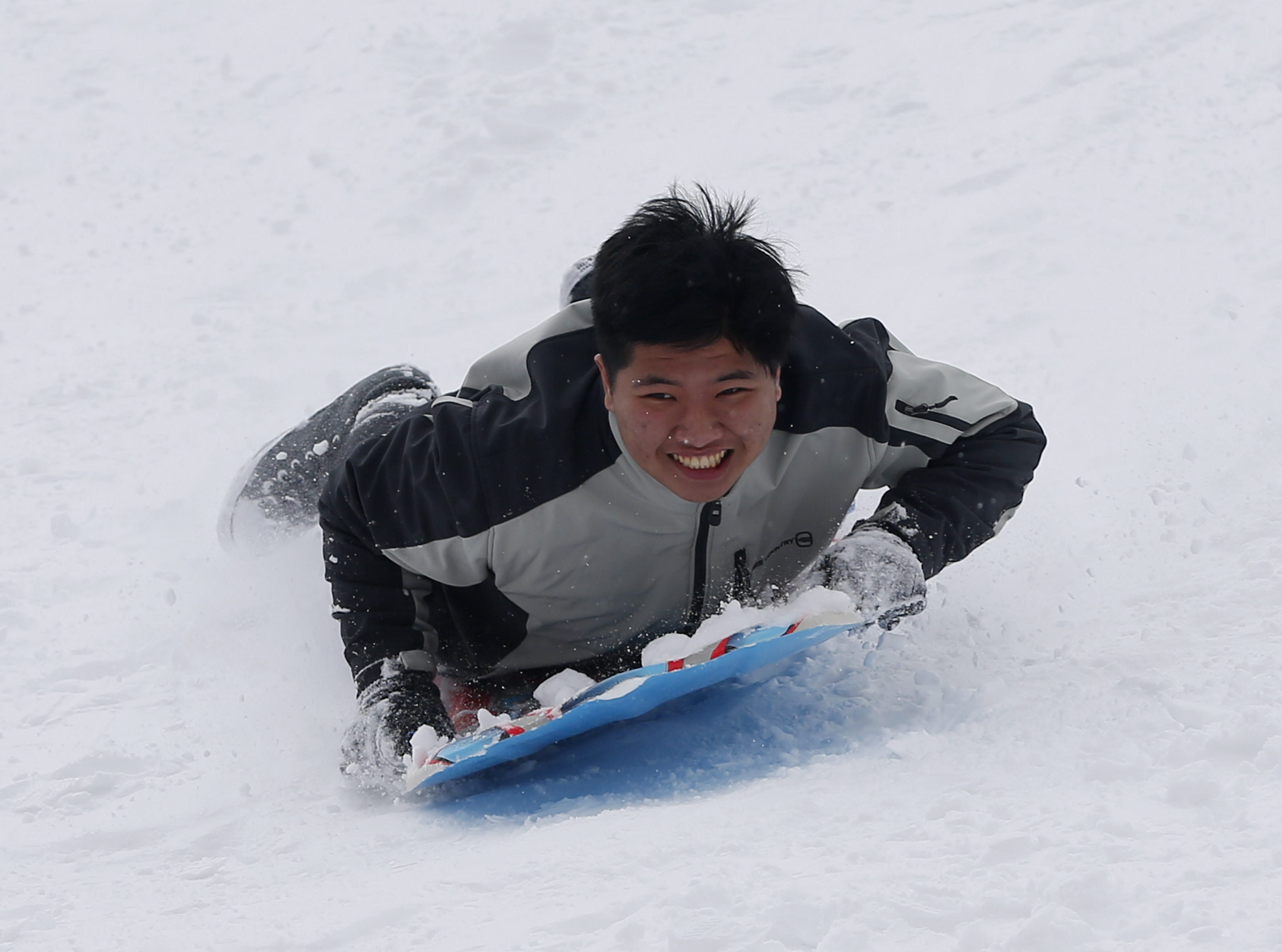 Khoi Bo, 16, slides down a hill in Flagstaff Feb. 18, 2019.