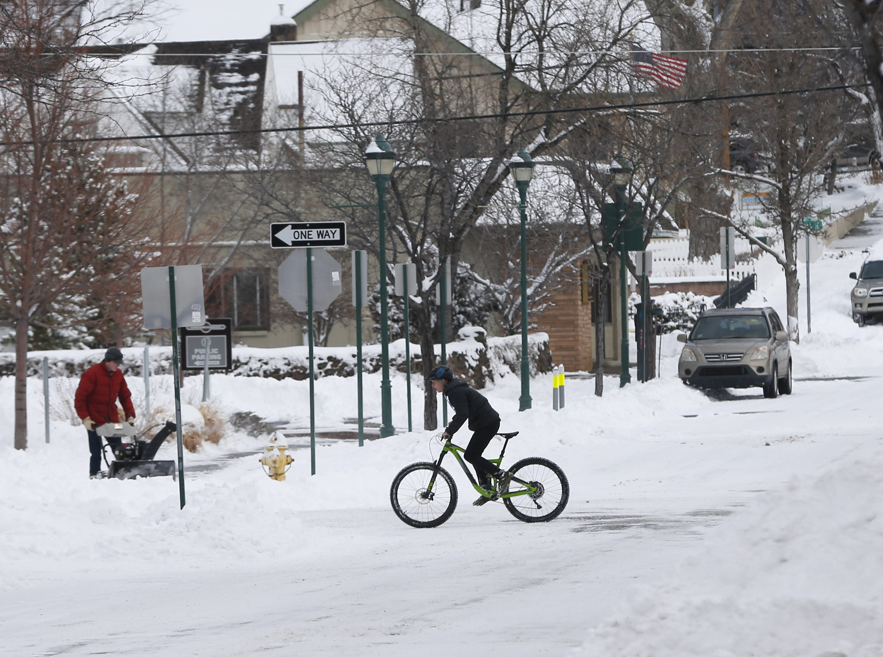 A cyclist rides his bike on Birch Ave. in downtown Flagstaff Feb. 18, 2019.