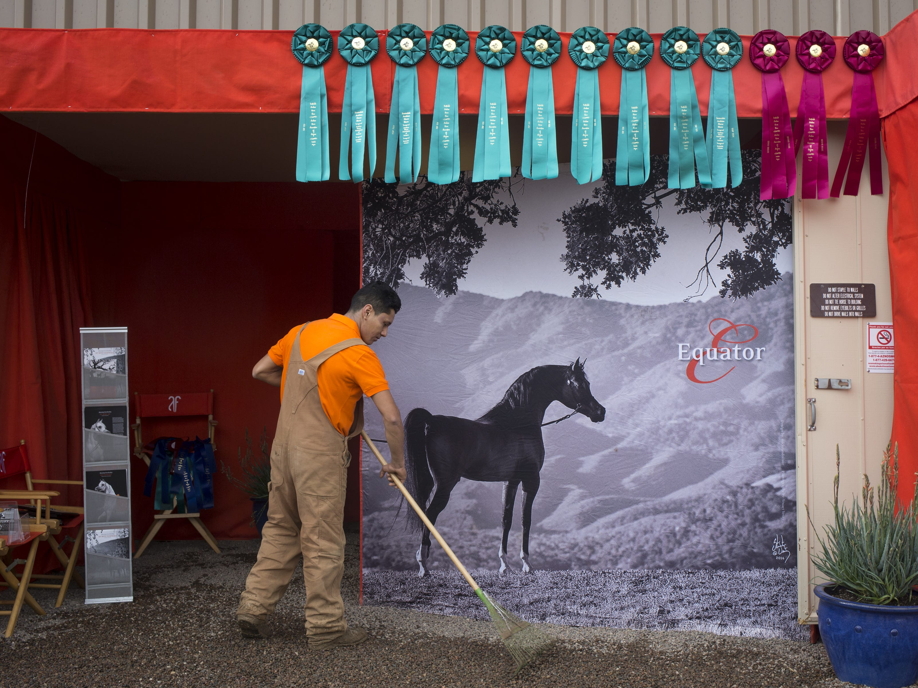 Ricky Barreto rakes in front of the Aljassimya Farms Stable on Feb. 18, 2019, at the 64th Annual Scottsdale Arabian Horse Show at West World.
