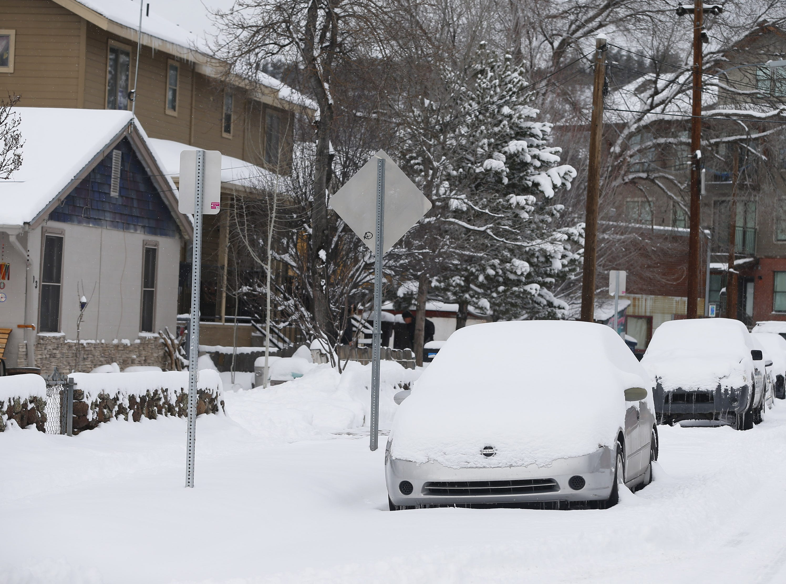 Parked cars are blanketed with fresh snow in Flagstaff Feb. 18, 2019.