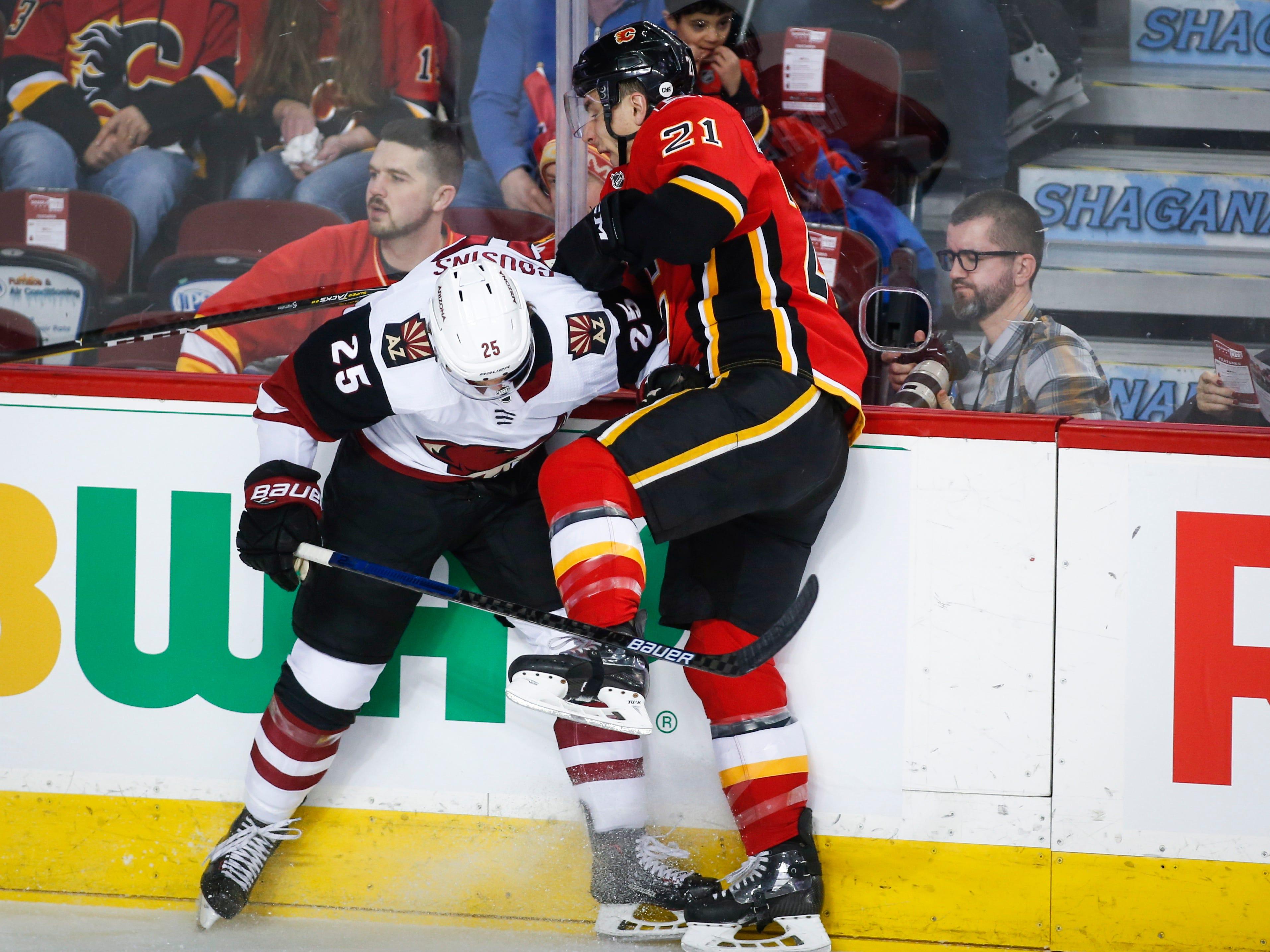 Arizona Coyotes' Nick Cousins, left, checks Calgary Flames' Garnet Hathaway during first period NHL hockey action in Calgary, Alberta, Monday, Feb. 18, 2019.