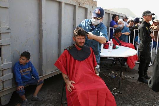 Migrantes centroamericanos reciben cortes de pelo en un albergue en Piedras Negras, Coahuila.