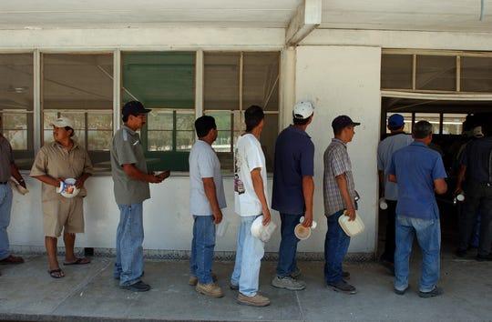 Reos de Islas Marías esperan en línea para recibir alimentos.