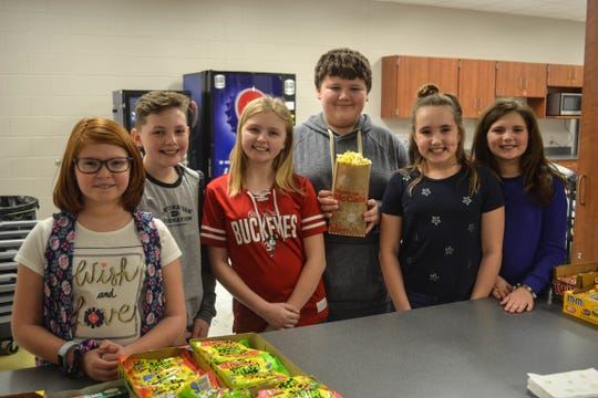 From left, Avery Philo, Chase Potridge, Emmaleigh Lawrence, Bryce Brzeczek, Ellison Dickman and Stella Strong, who donate their time to man the concession stand at Woodmore Middle School during home sporting events. The group has invested countless volunteer hours and donate 100 percent of popcorn sales to Susie's Coats.